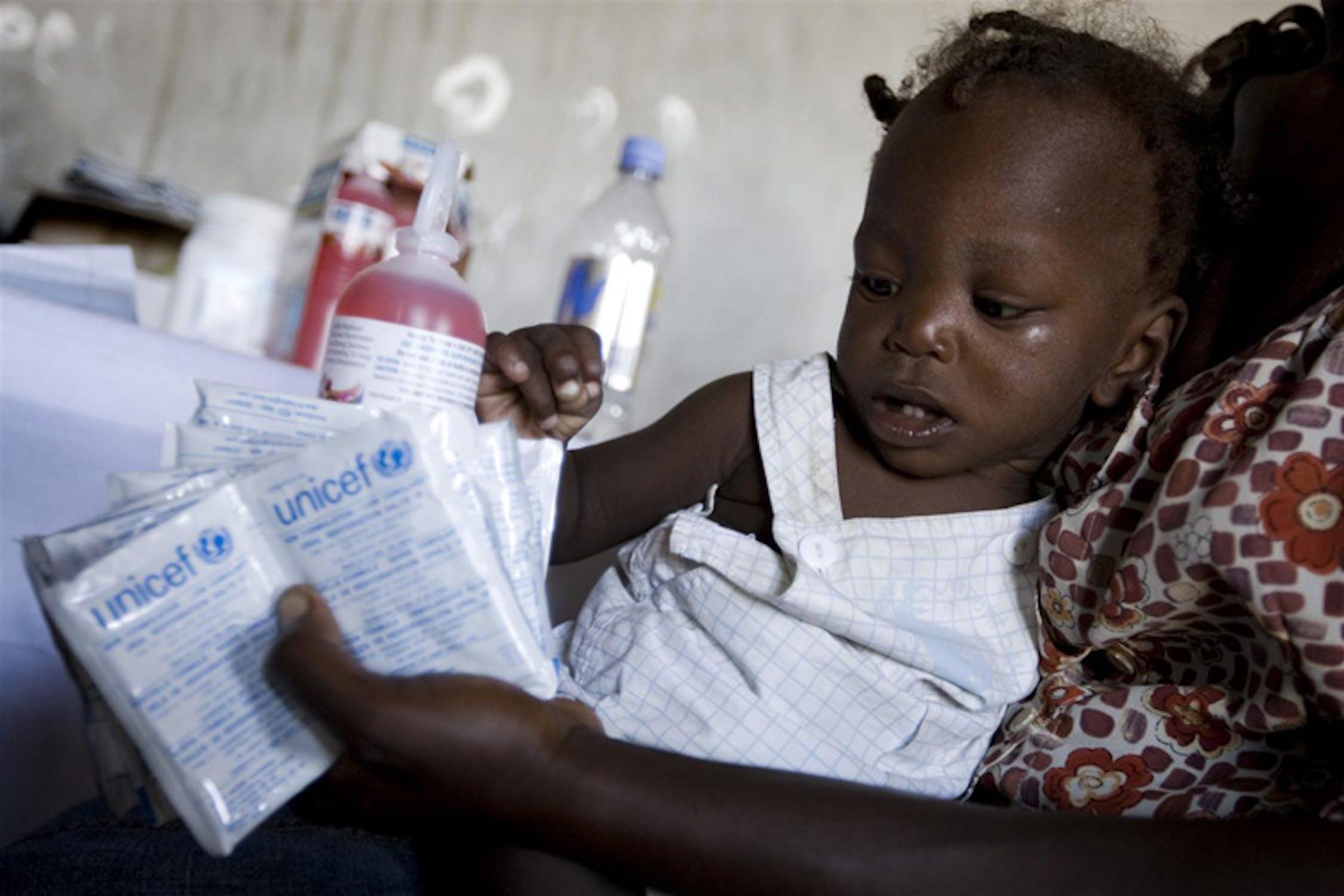 Una madre col suo bambino nell'accettazione dell'ospedale di Grand Dessalines, Haiti: nella sua mano, alcune bustine di sali reidratanti per contrastare la diarrea acutissima provocata dal colera