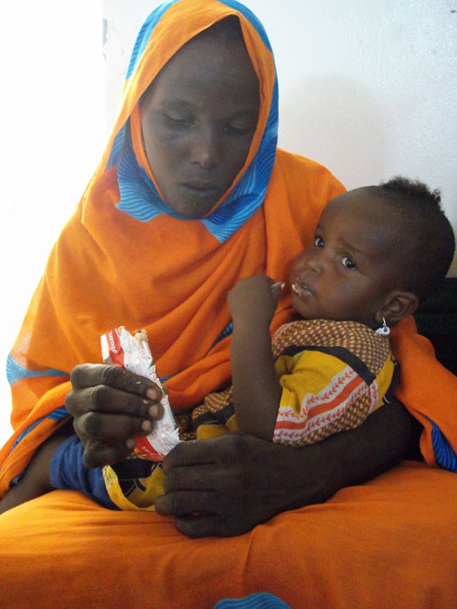 Questo bambino, in braccio alla mamma, mangia il Plumpynut, alimento terapeutico pronto per l'uso. ©Saira Cutrone