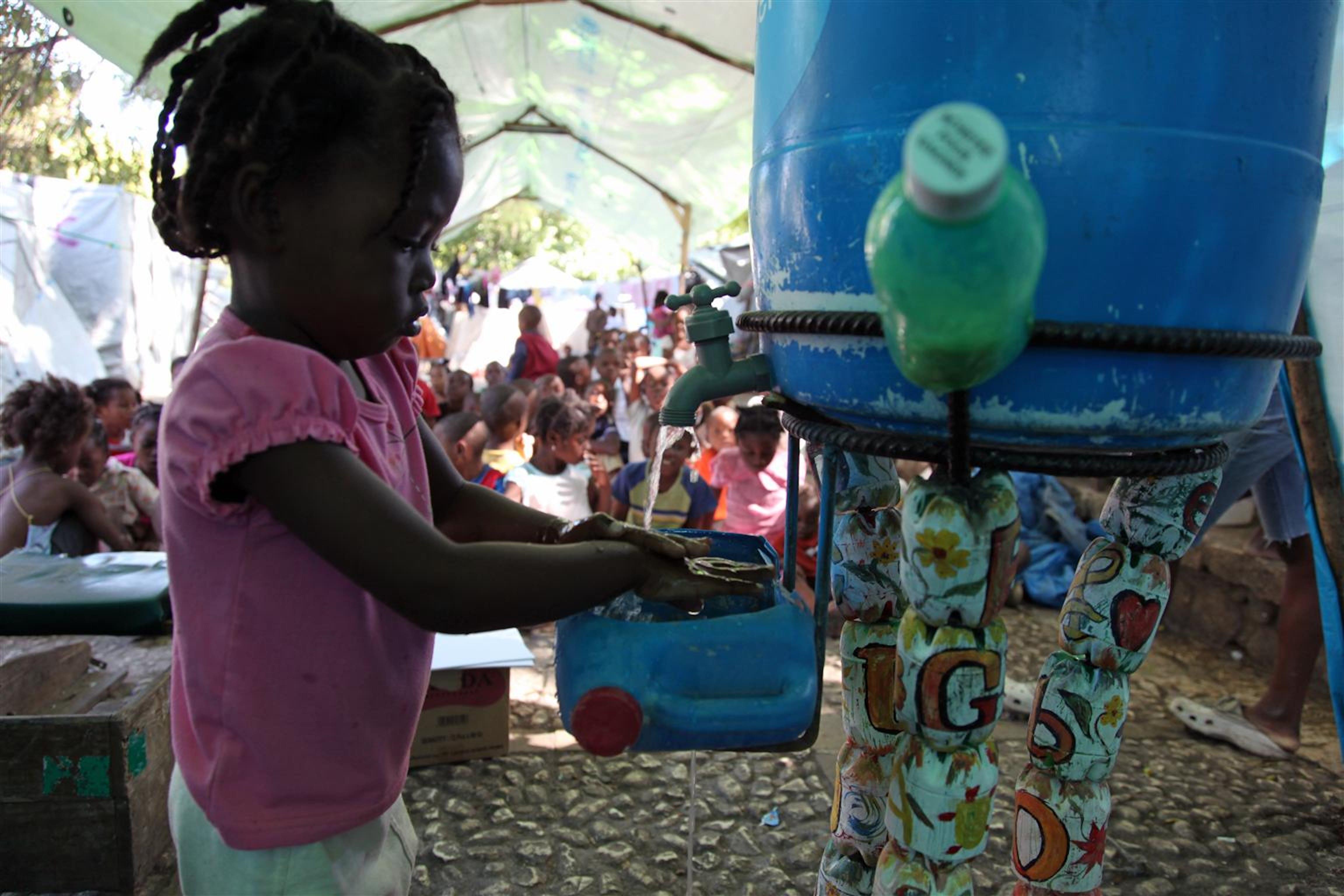 Una bambina prende l'acqua da una cisterna installata dall'UNICEF nel campo per sfollati di Pétionville, un quartiere della capitale di Haiti - ©UNICEF/NYHQ2010-2665/R.LeMoyne