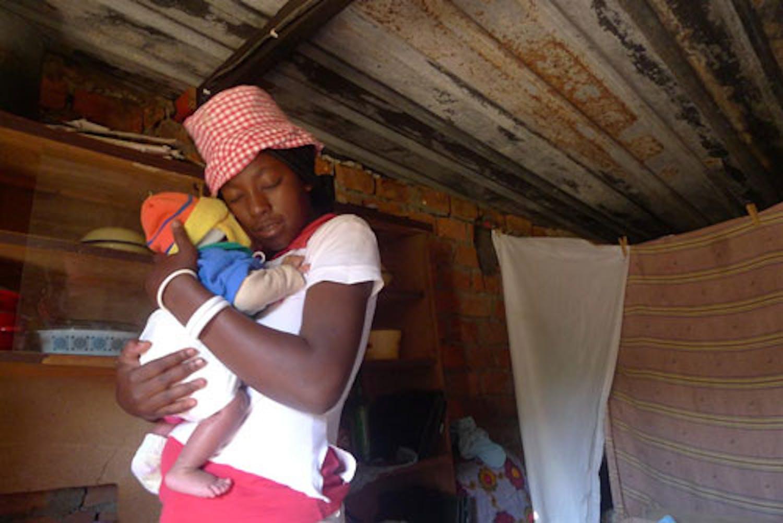 Questa mamma coccola il suo bambino nella loro casa alla periferia di Lusaka (Zambia). Ha scoperto di essere sieropositiva mentre era incinta, e ora partecipa al programma di prevenzione della trasmissione madre-figlio dell'HIV.