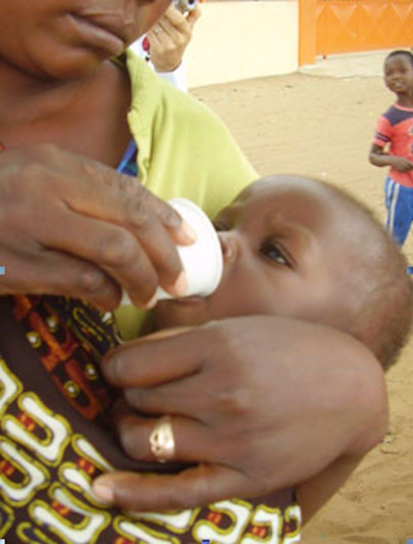 Una mamma aiuta a dare Albendazol (anti parassitaro) sciolto nell'acqua al suo bambino. ©Manuela Cau