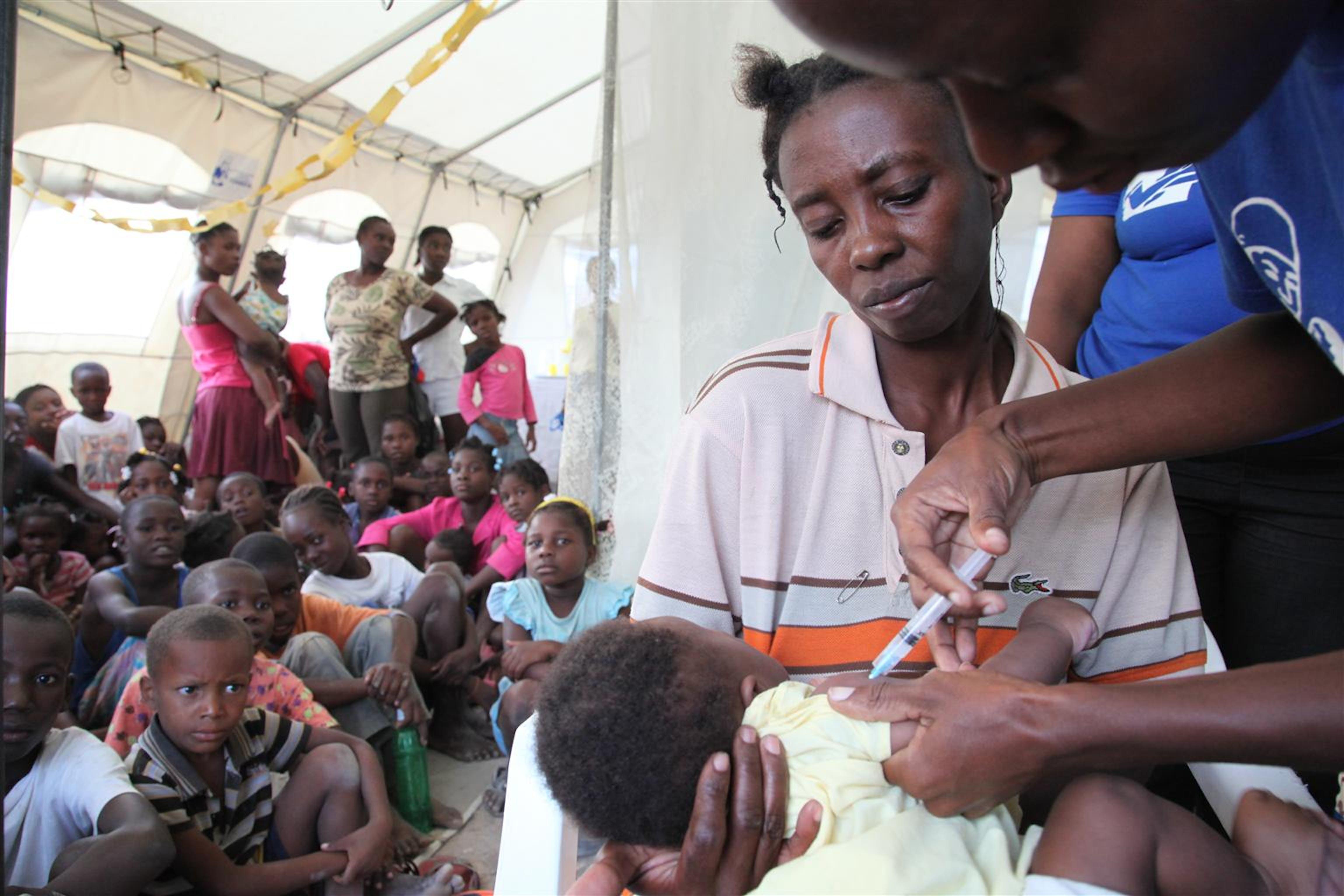 Haiti. Un bambino in braccio alla sua mamma viene vaccinato in una clinica mobile allestita dopo il terremoto©UNICEF/NYHQ2010/LeMoyne