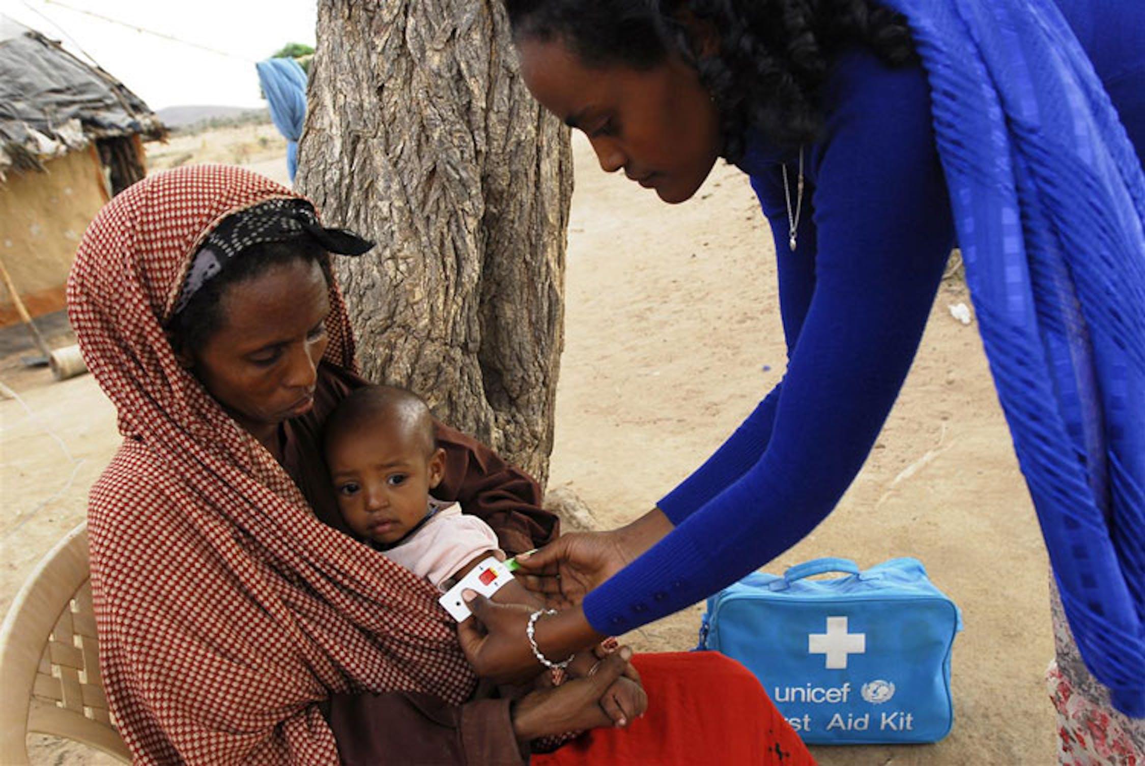 Meleb (Etiopia): un'operatrice misura lo stato di malnutrizione della piccola Firdoze, 10 mesi, utilizzando l'apposito braccialetto denominato MUAC - ©UNICEF/NYHQ2011-1329/Getachew