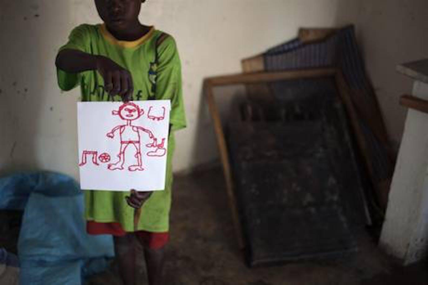 Un bambino ospite del centro dell'UNICEF mostra orgoglioso il suo disegno