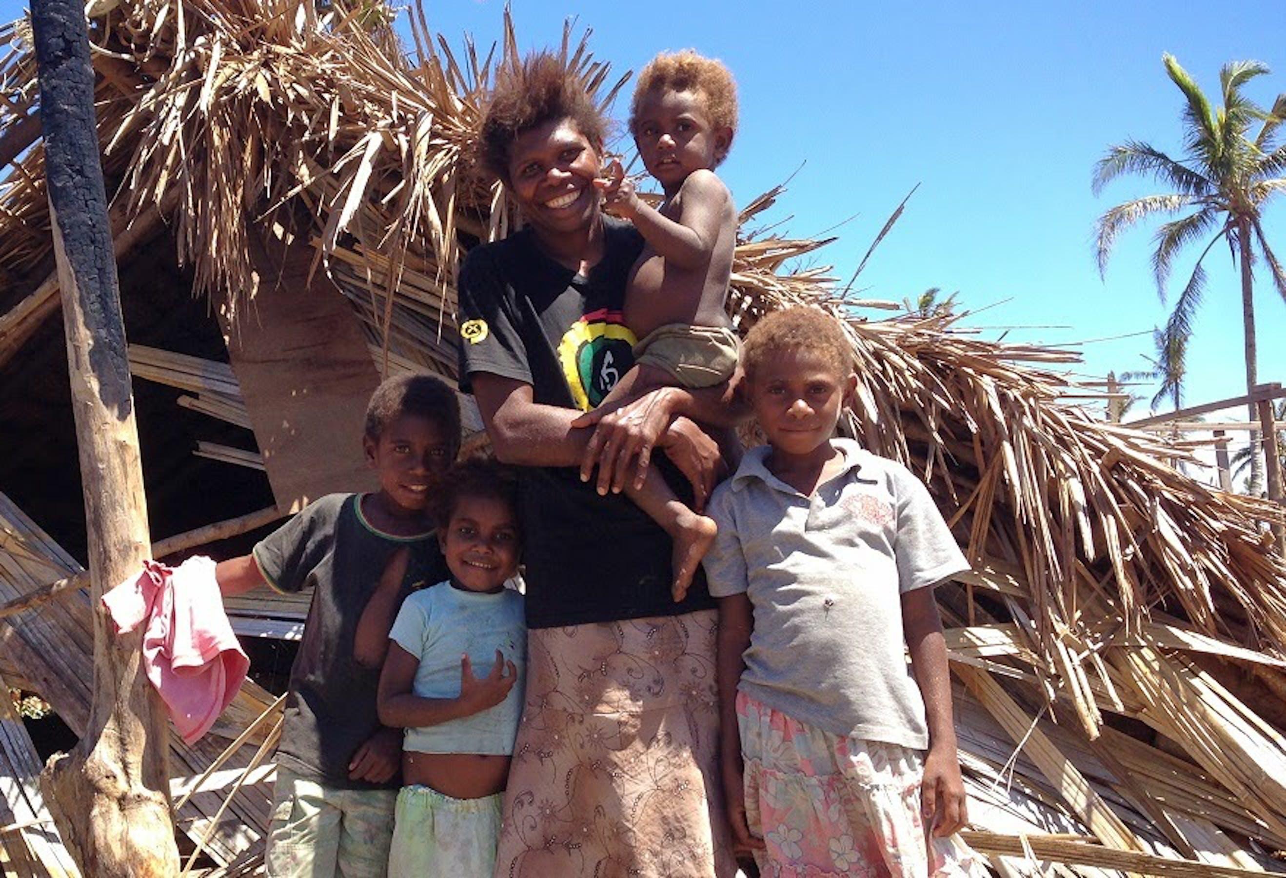 Una famiglia sull'isola Tannu sorride, nonostante la distruzione della sua abitazione - ©UNICEF Pacific/2015/Crumb