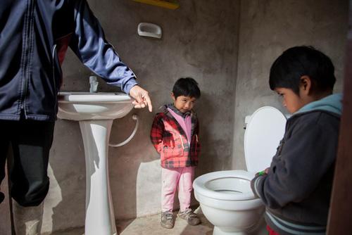 Porfirio Visalla insegna l'uso dei nuovi sanitari ai gemellini Jeremias e Mateo, 3 anni. La famiglia Visalla appartiene all'etnia Guaranì, la più importante della Bolivia. Fino a poco tempo fa in questa comunità non c'erano gabinetti, e spesso gli abitanti erano stati morsi da serpenti mentre facevano i bisogni all'aperto - ©UNICEF/NYHQ2015-1923/Gilbertson VII