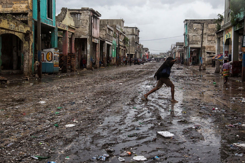 Una donna attraversa una strada allagata a Port-au-Prince, capitale di Haiti - ©UNICEF/UN034468/Abassi/UN MINUSTAH