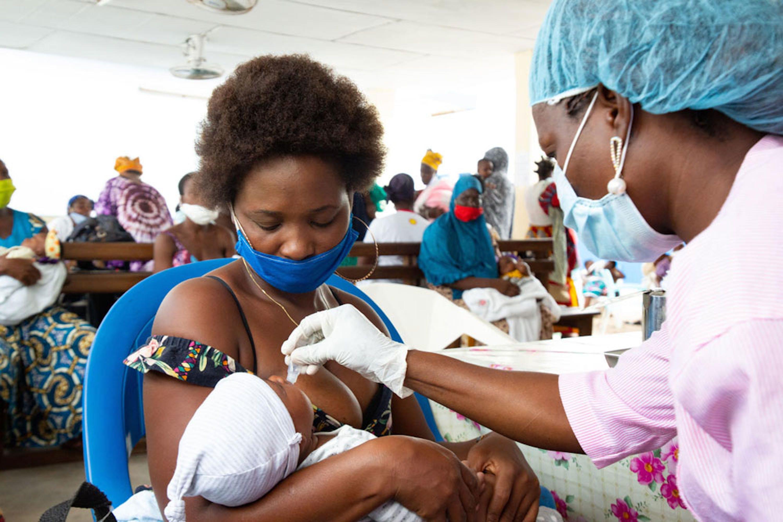 Vaccinazione antipolio di una neonata nell'ospedale di Gonzagueville, sobborgo di Abidjan, capitale della Costa d'Avorio. Mamma e operatrice sanitaria indossano mascherine per proteggersi dal COViD-19 - ©UNICEF/UNI329334/Diarassouba