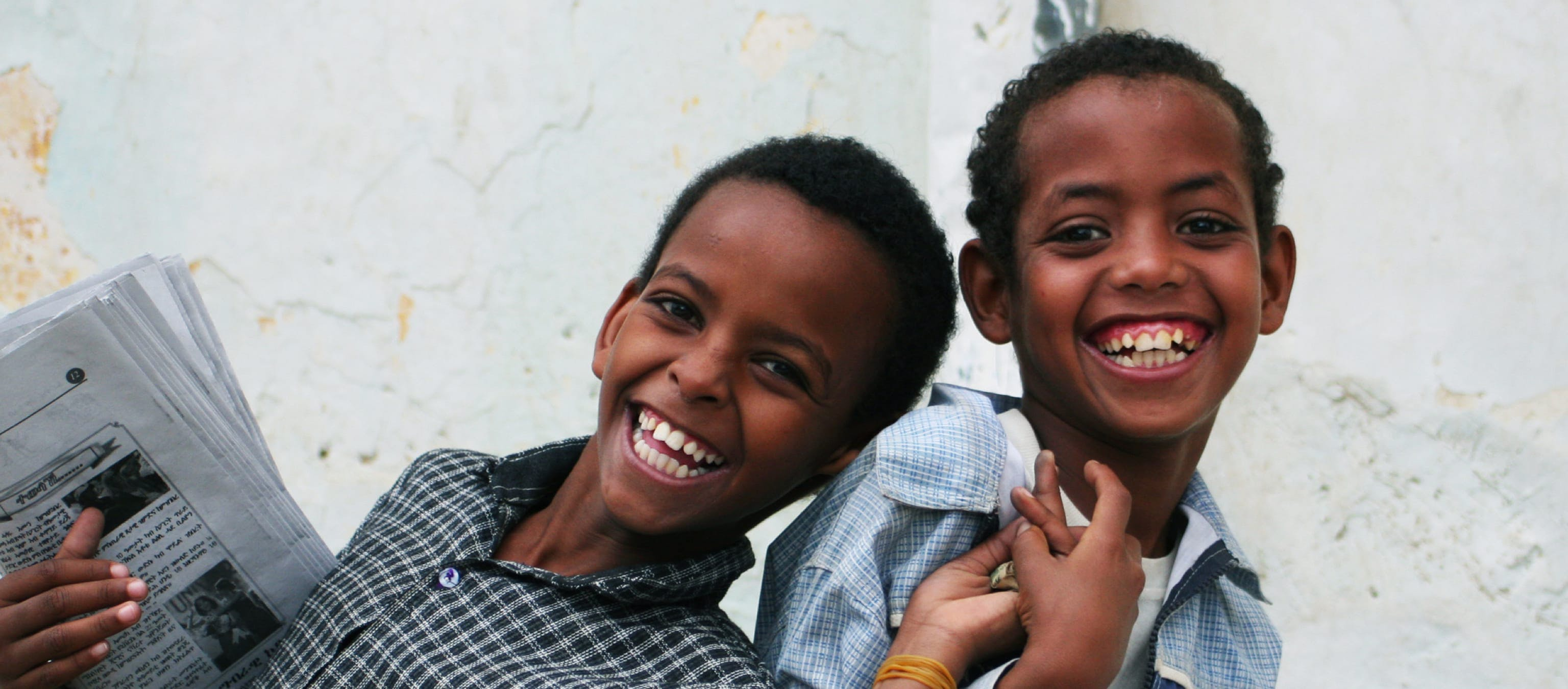 Due bambini sorridono con in mano un giornale
