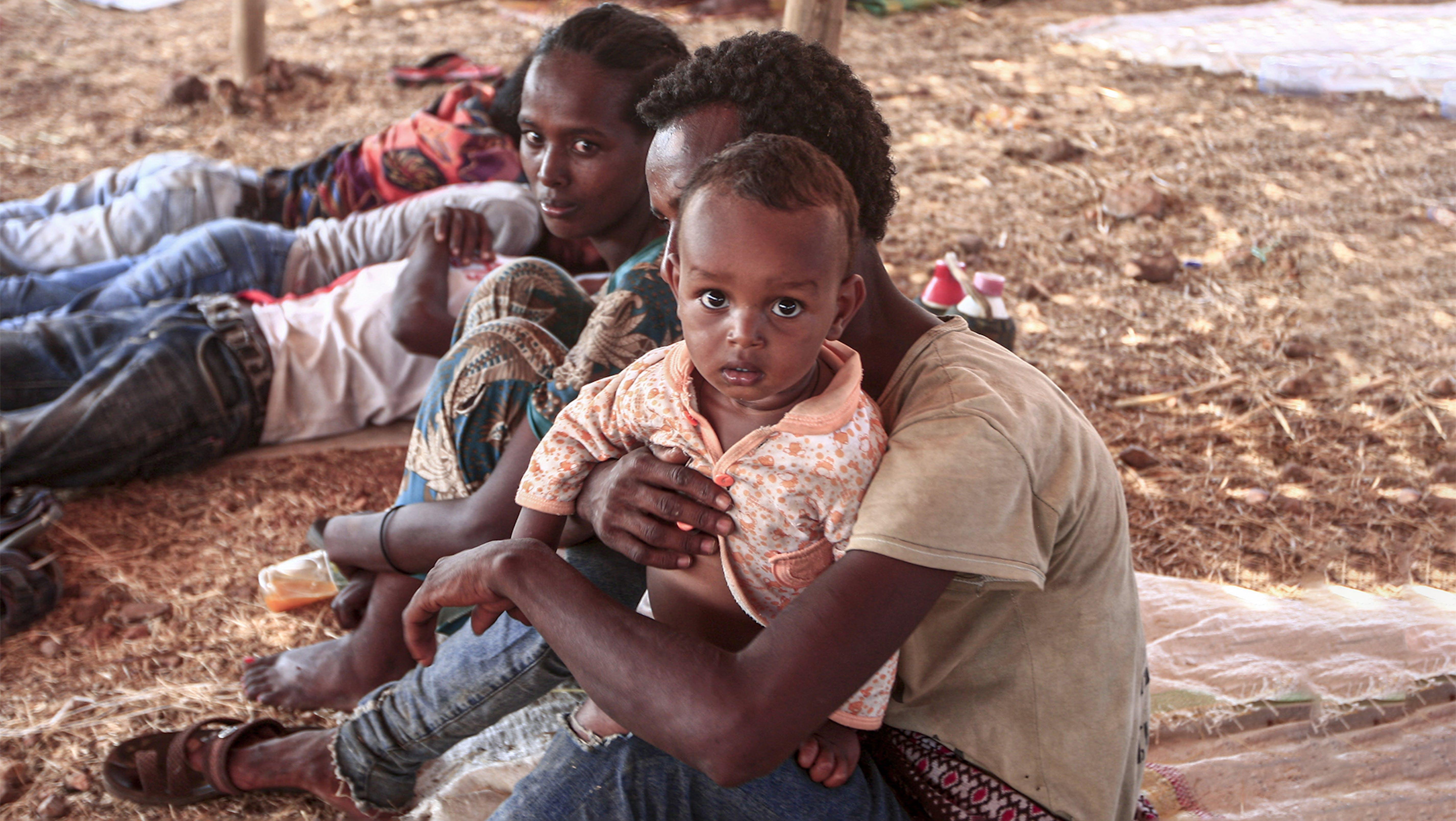 Un bambino rifugiato etiope in braccio a suo papà  © UNICEF/UN0371488/Hamid/AFP Non utilizzabile da media e partner