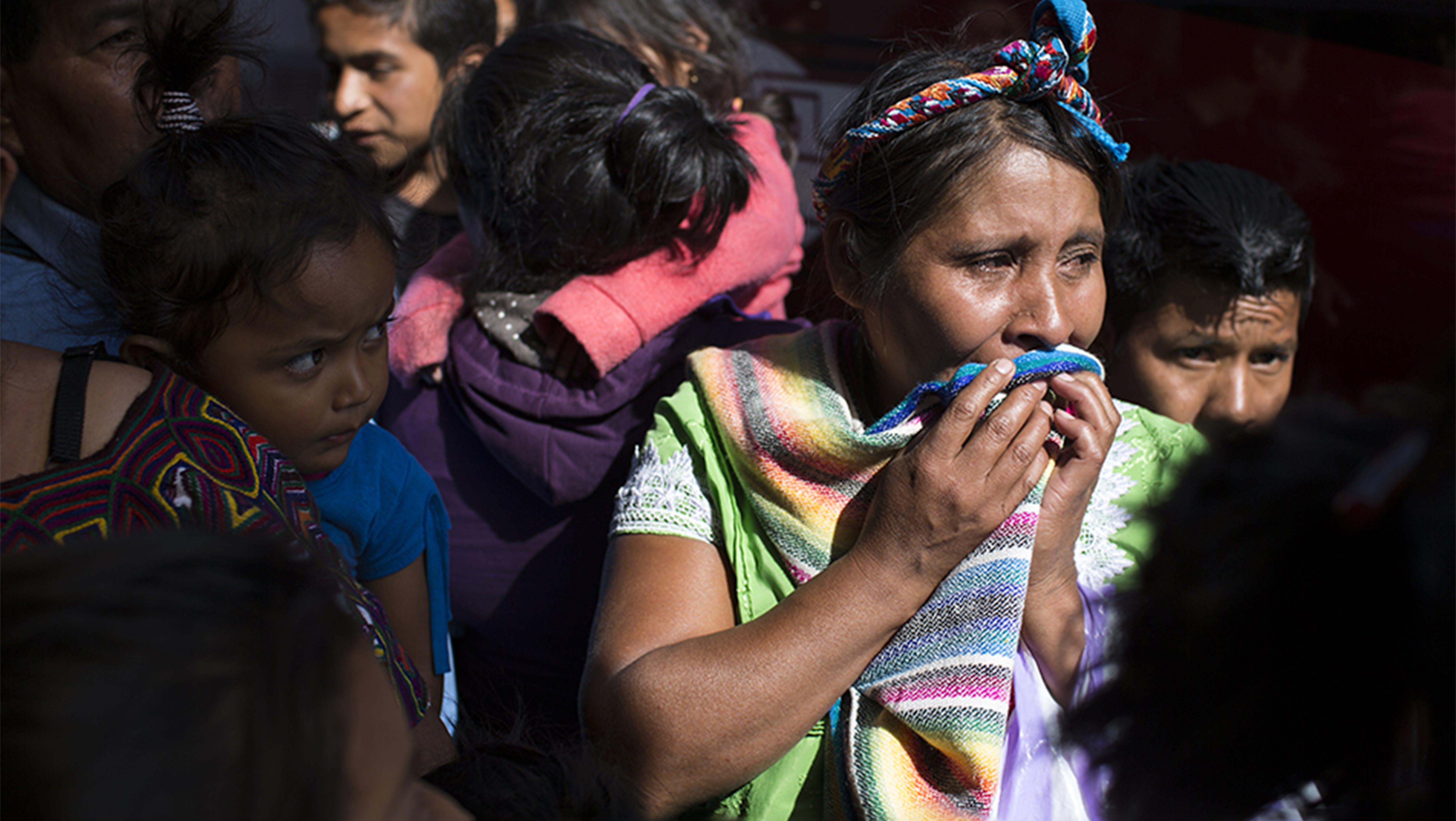 Una migrante fuggita dalla sua casa piange dopo aver rivisto suo figlio