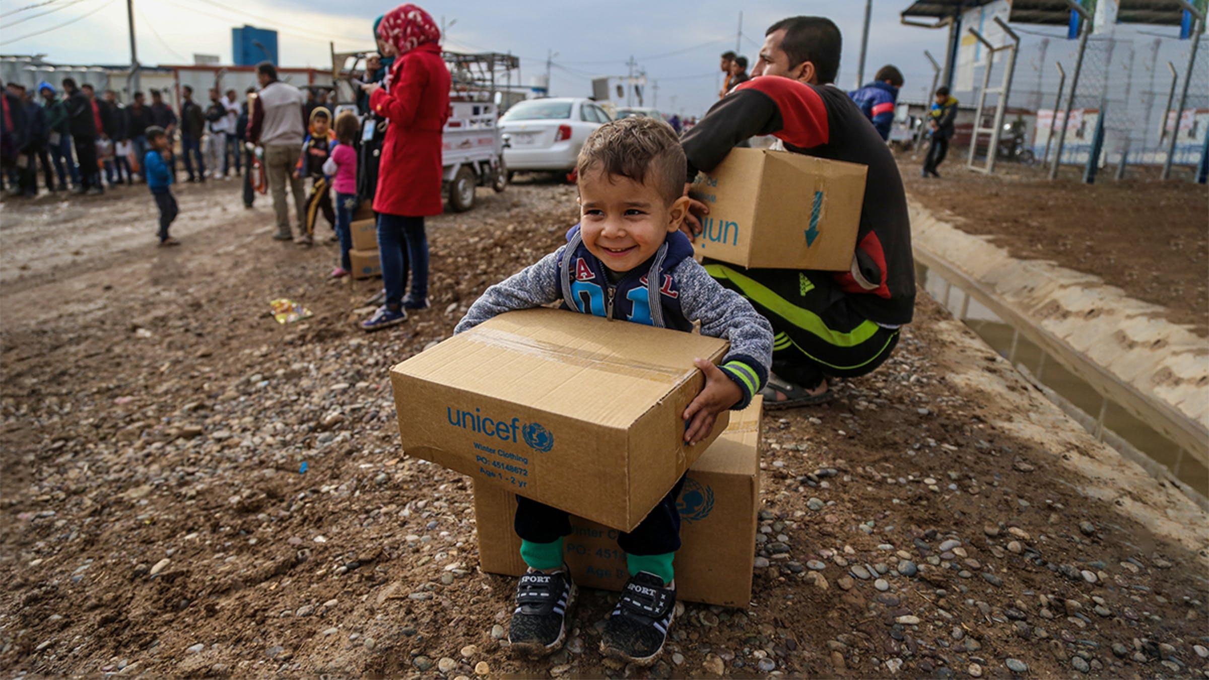 un bambino sorride per il pacco di aiuti ricevuti