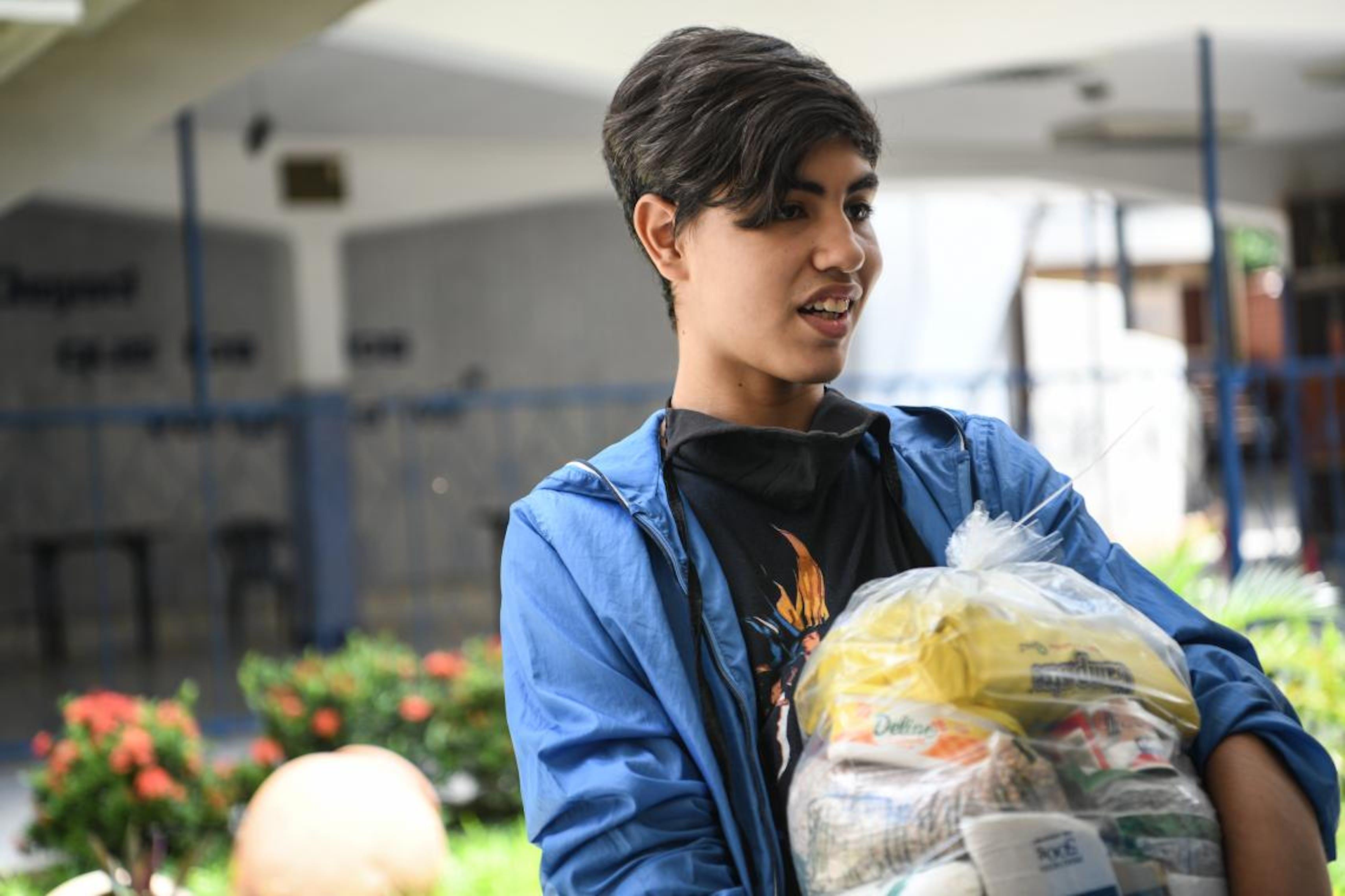 Fernando, 17 anni, riceve un pacco alimentare a scuola, alla periferia di Caracas.