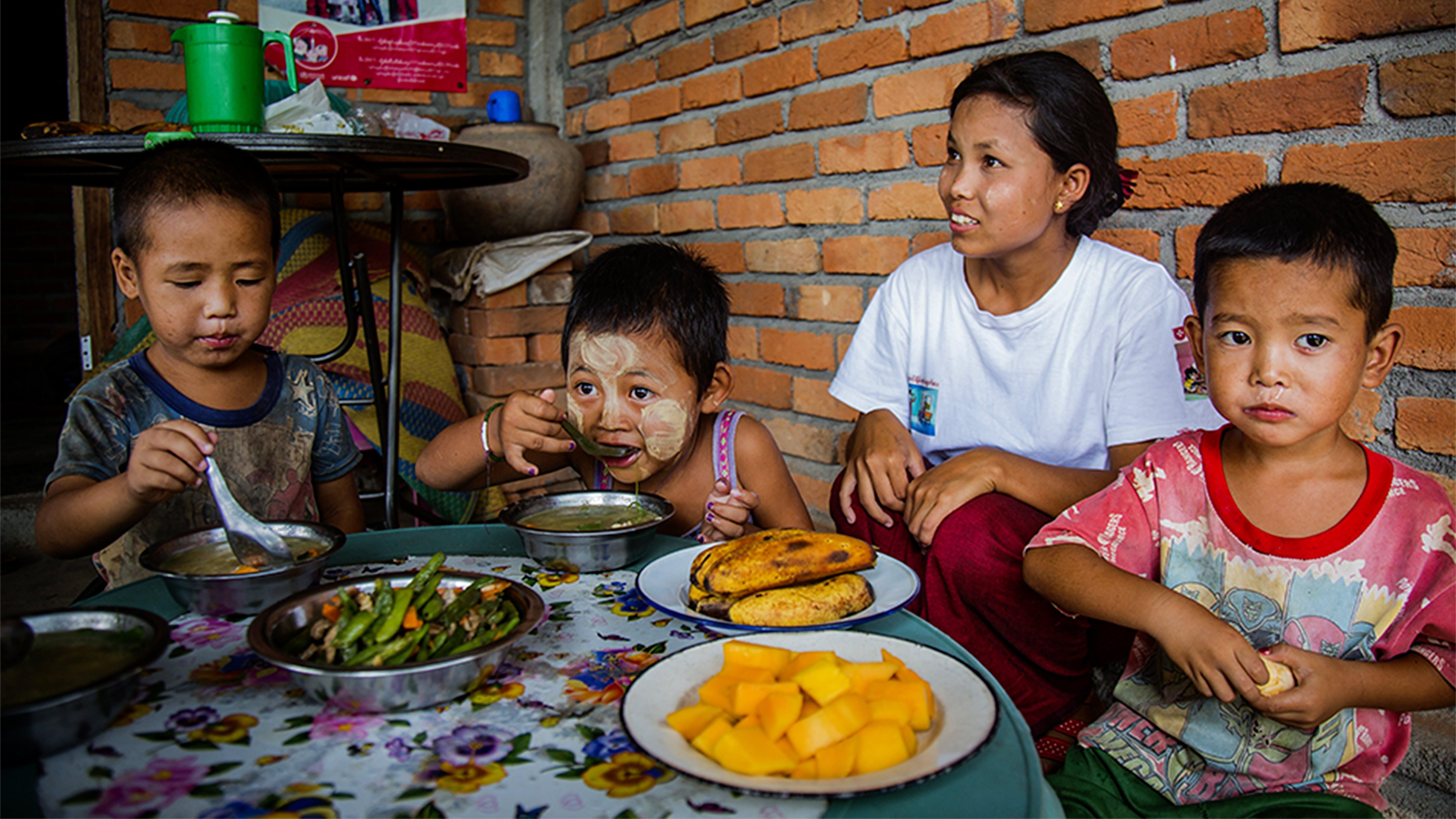 Alcuni bambini si nutrono con del cibo cucinato da operatori sanitari volontari