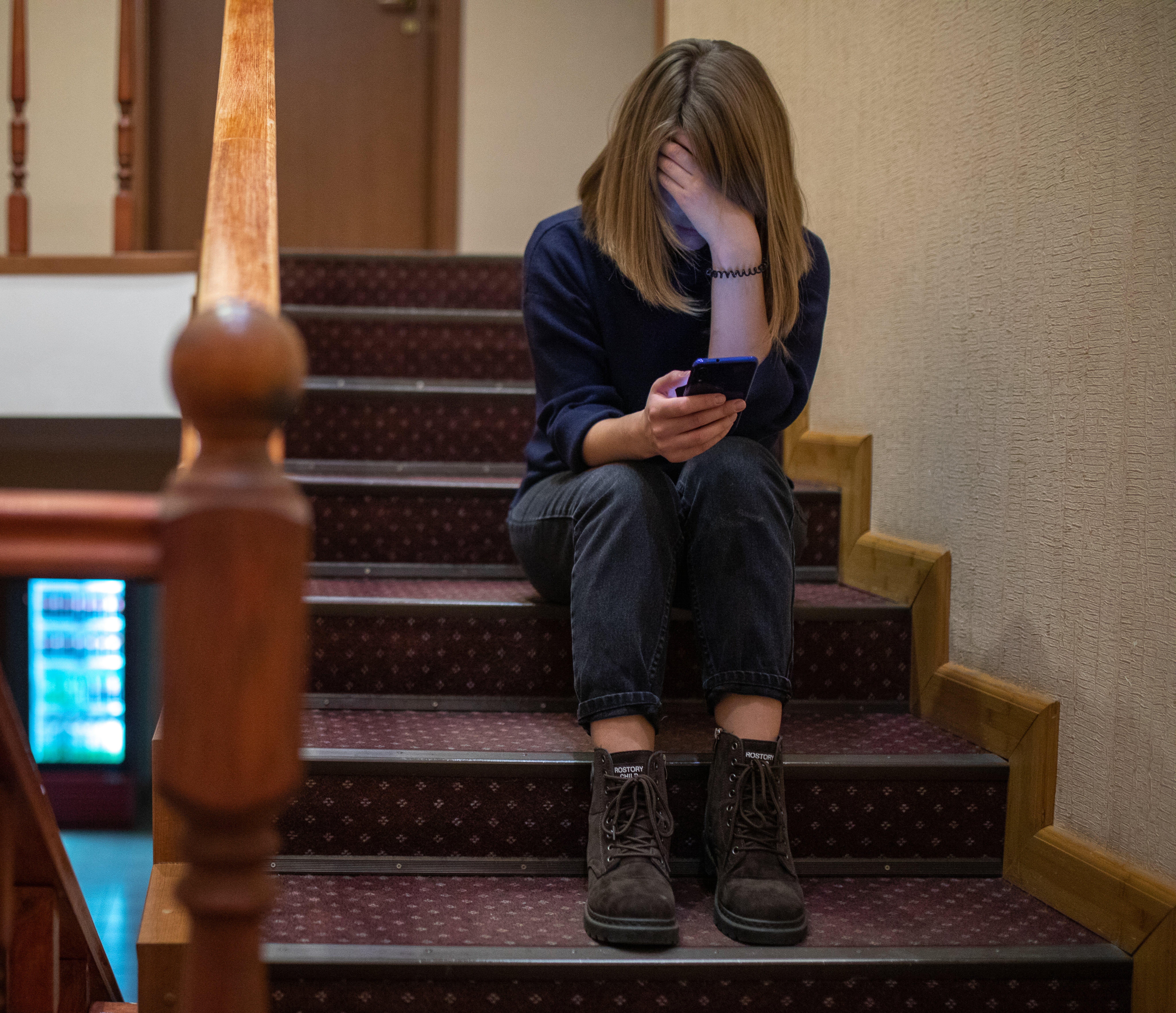Ucraina, Valia, 15 anni, è seduta sulle scale mentre guarda il suo cellulare