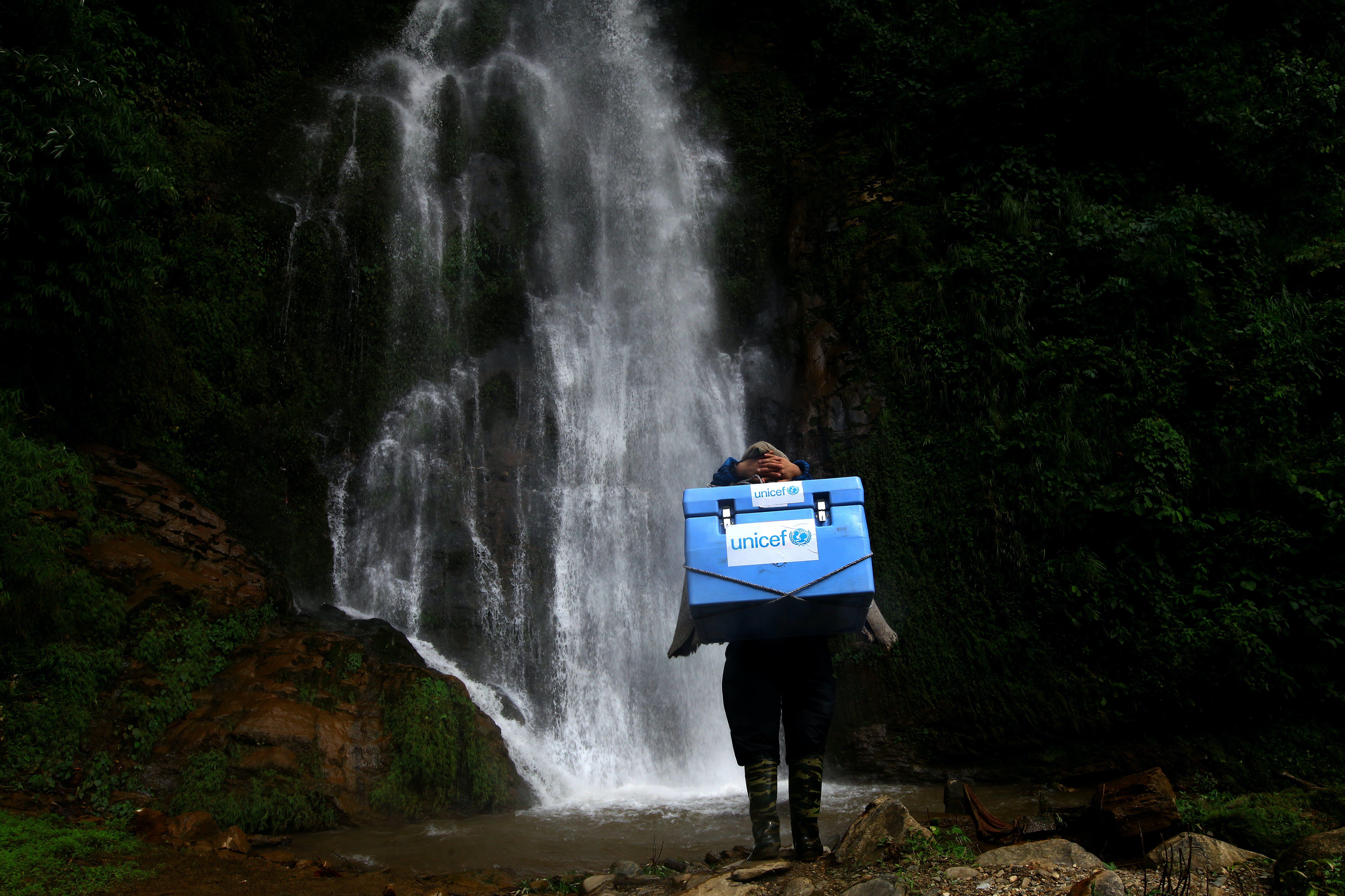 Nella foto, un operatore trasporta i vaccini forniti dall'UNICEF attraverso un sentiero impervio