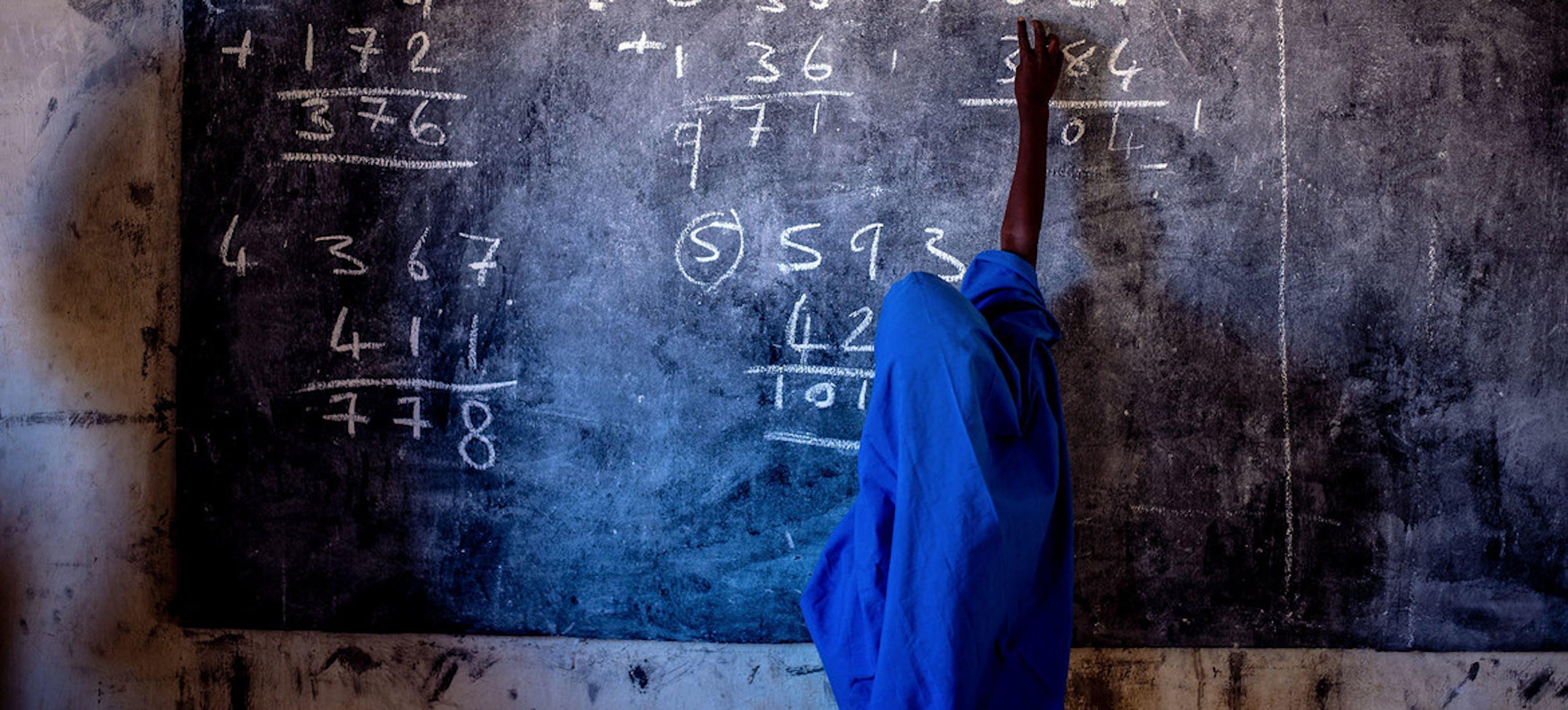 Una ragazza scrive su una lavagna in una scuola elementare in Nigeria
