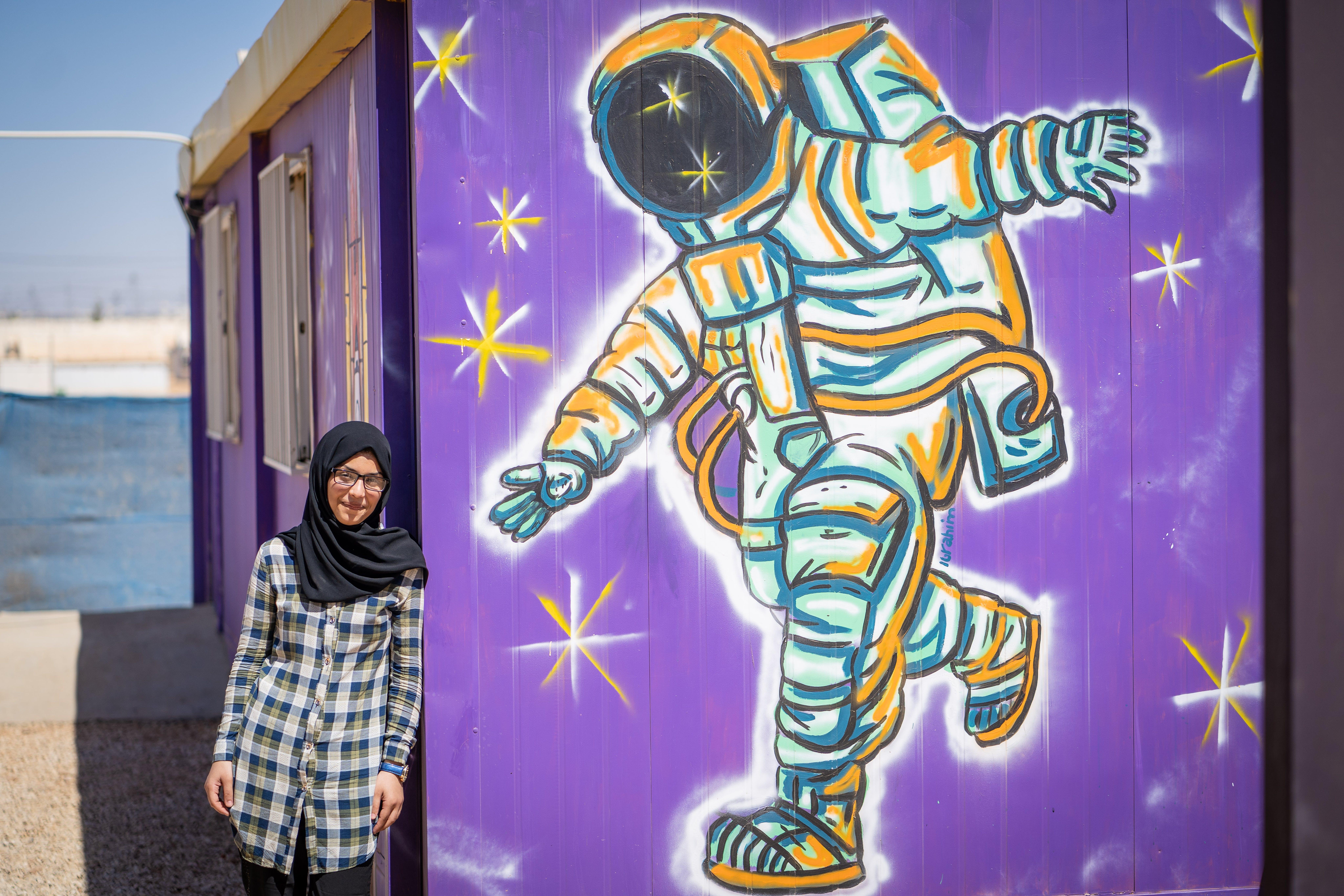 Bodoor, rifugiata siriana il cui sogno è diventare astronauta, accanto a un murales