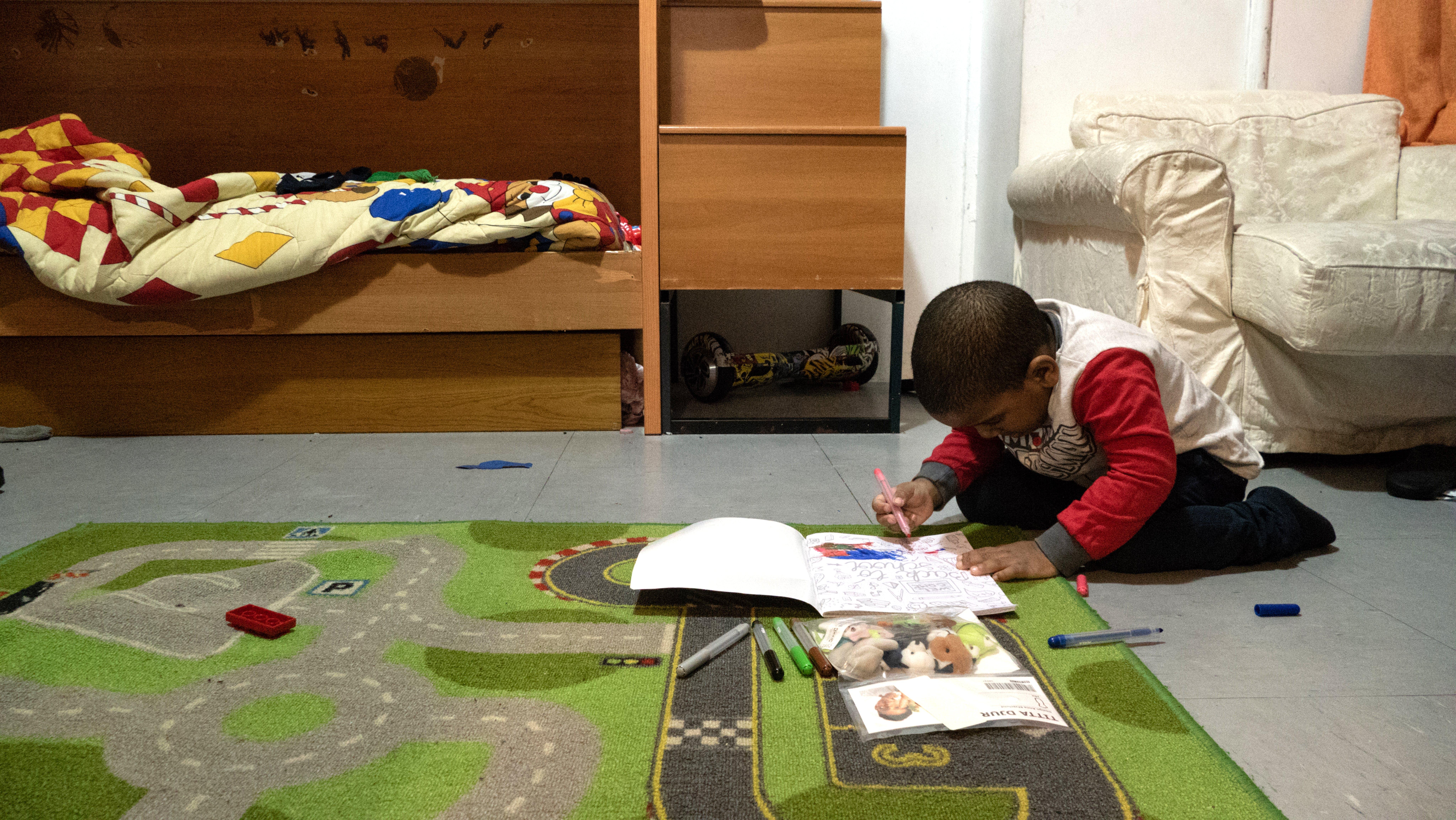 Il figlio minore di Josy disegna, seduto a terra: anche lui ha avuto il COVID ed è stato supportato da UNICEF