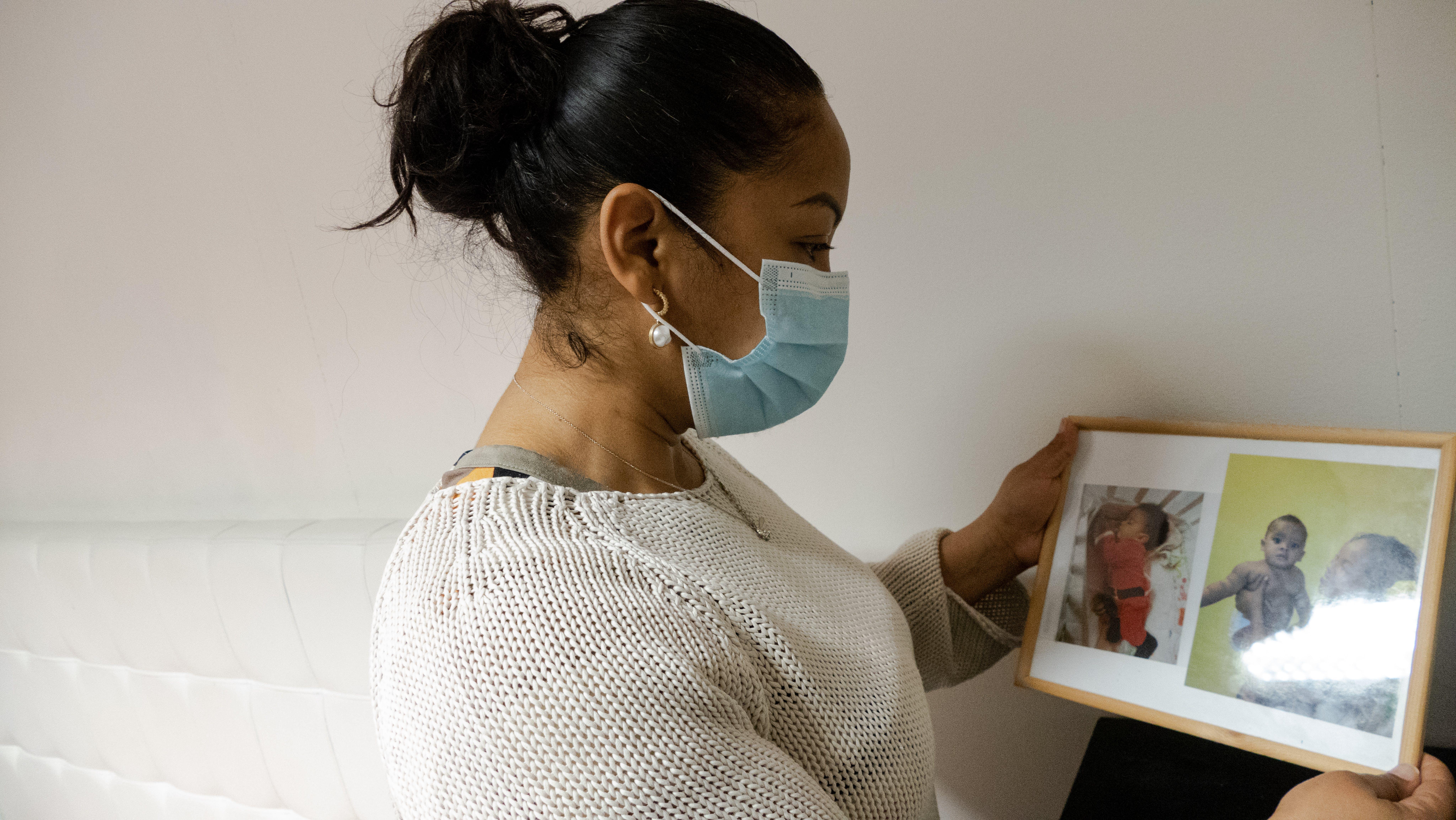 Josy, che vive in una casa occupata, mostra le foto di famiglia agli operatori UNICEF-Intersos