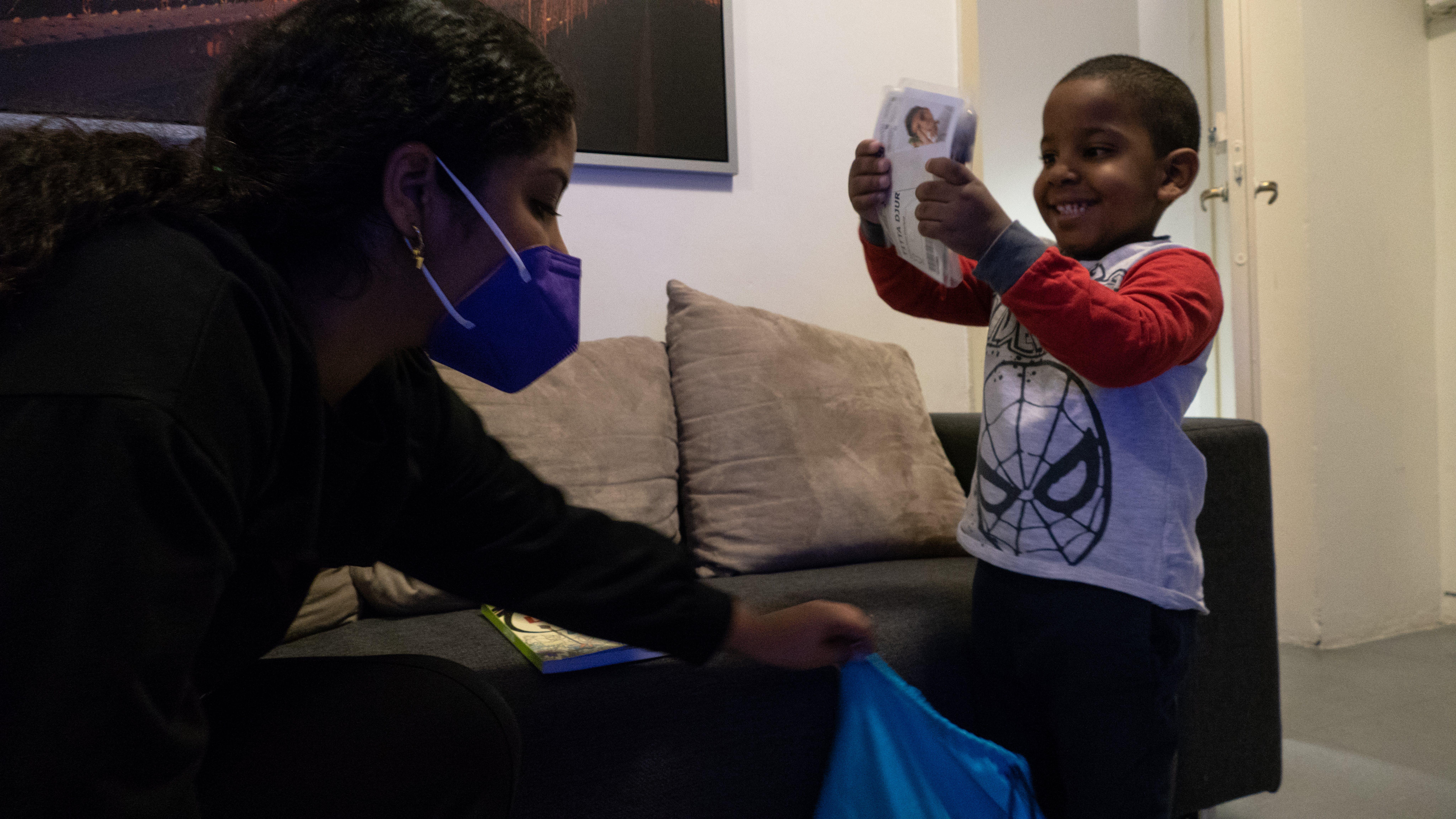 Alexis, il piccolo della famiglia, sorride aprendo il pacco ricevuto da UNICEF-Intersos