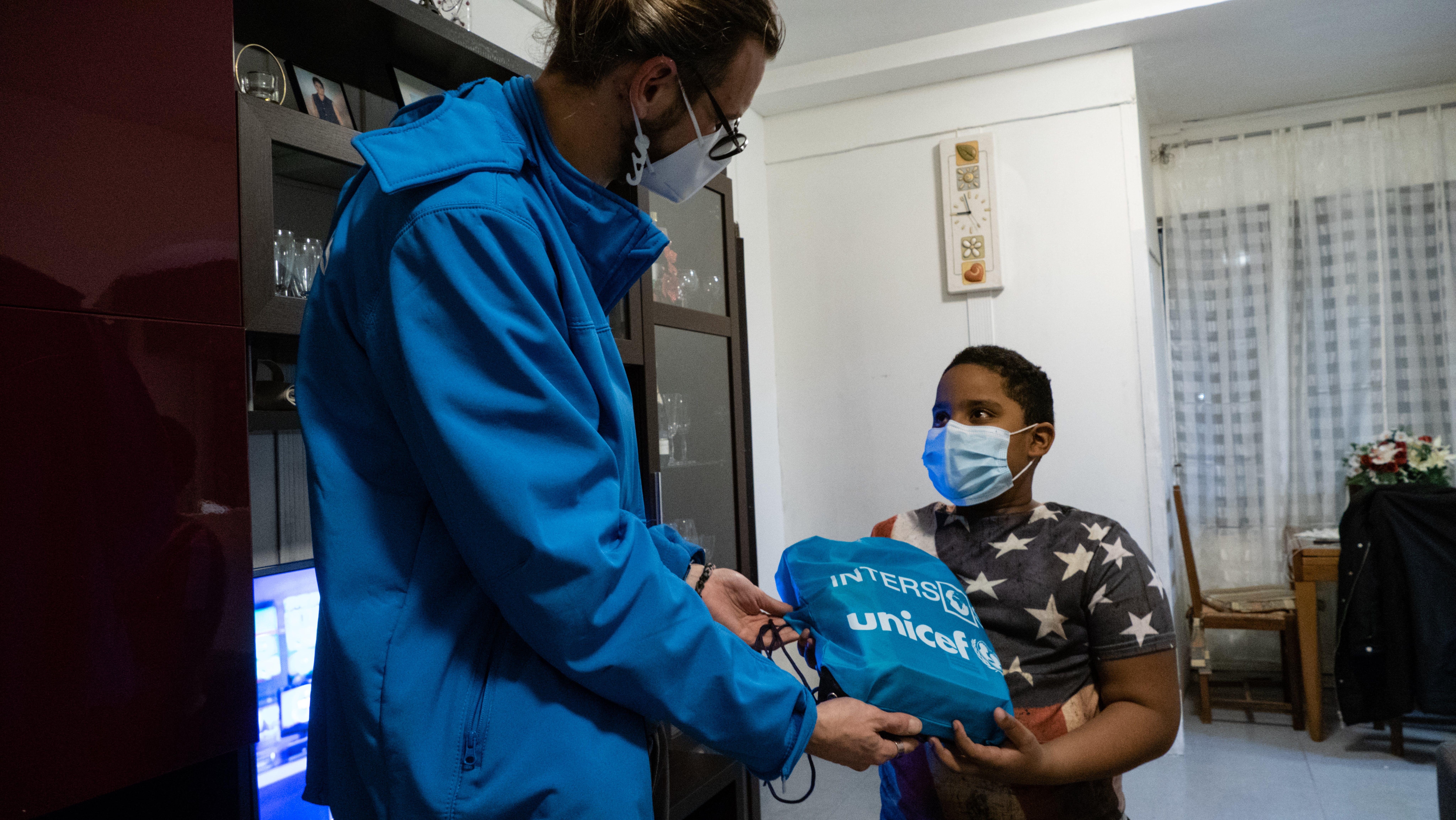 Daniel, il secondo genito, riceve il sacchetto con materiali preparati da UNICEF-Intersos