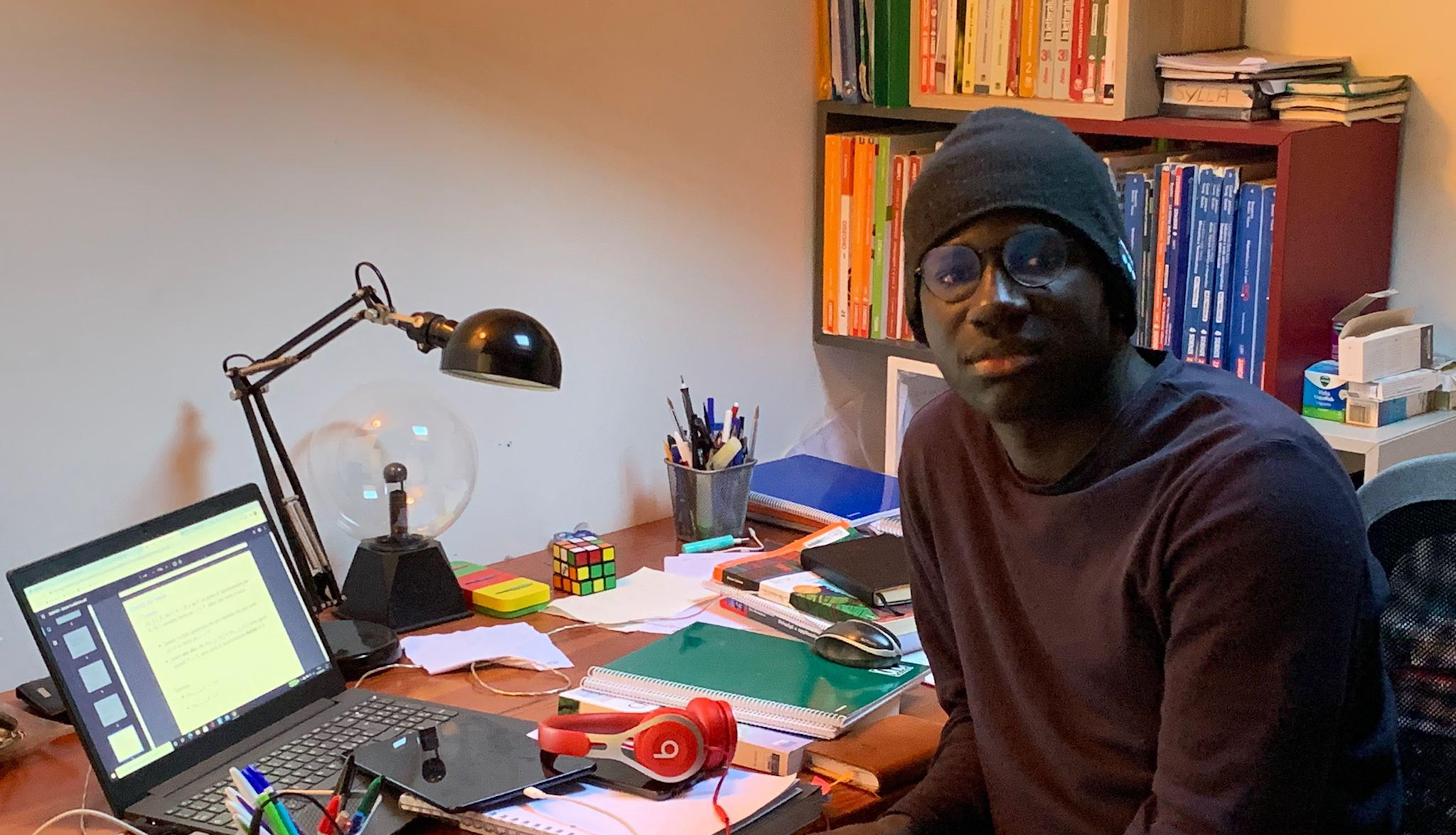 Almamy studia nella sua stanza, nella casa di Milano in cui vive con la sua famiglia affidataria