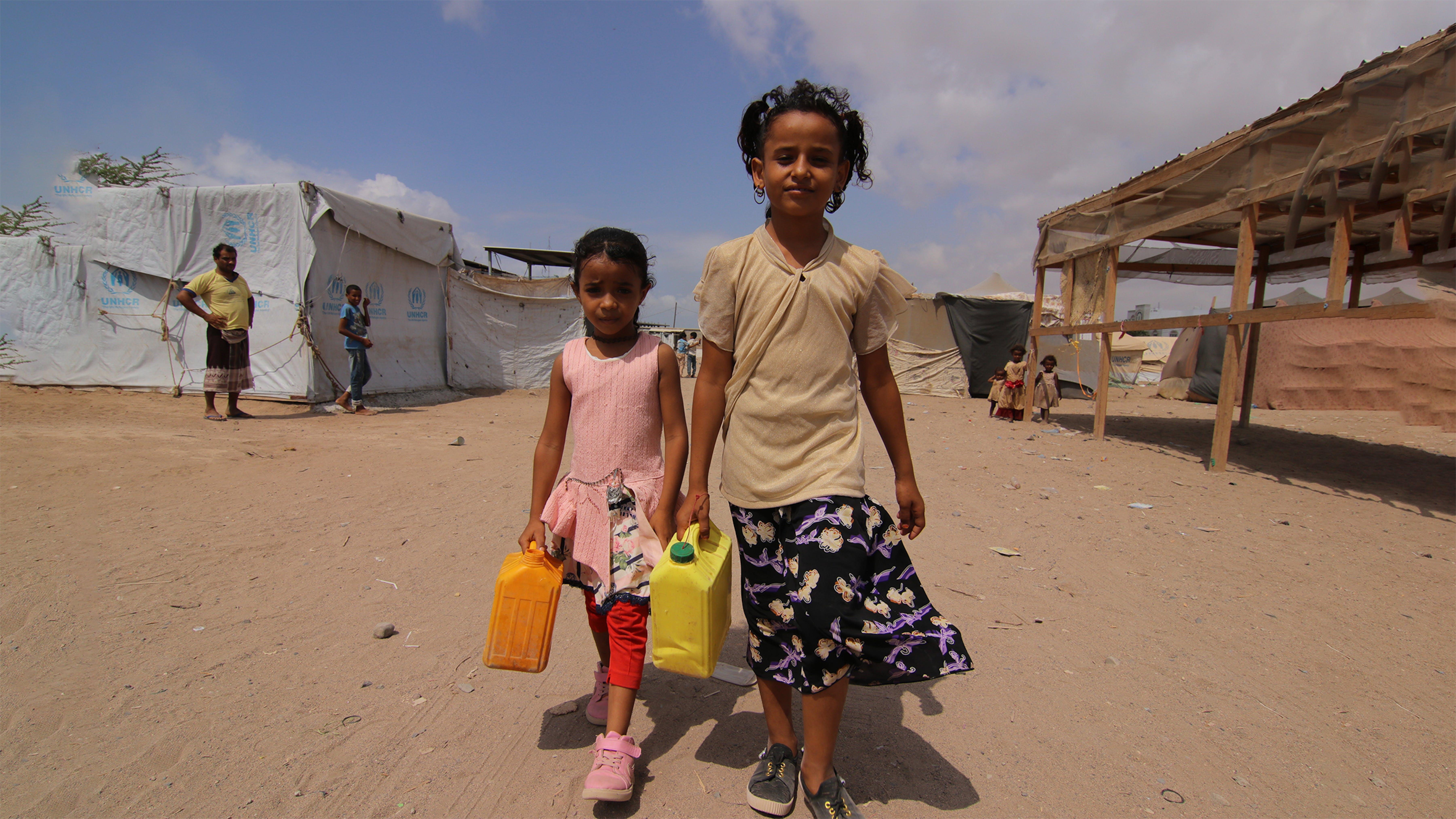 Yemen: due bambine camminano con i serbatoi attraverso un campo sfollati ad Aden