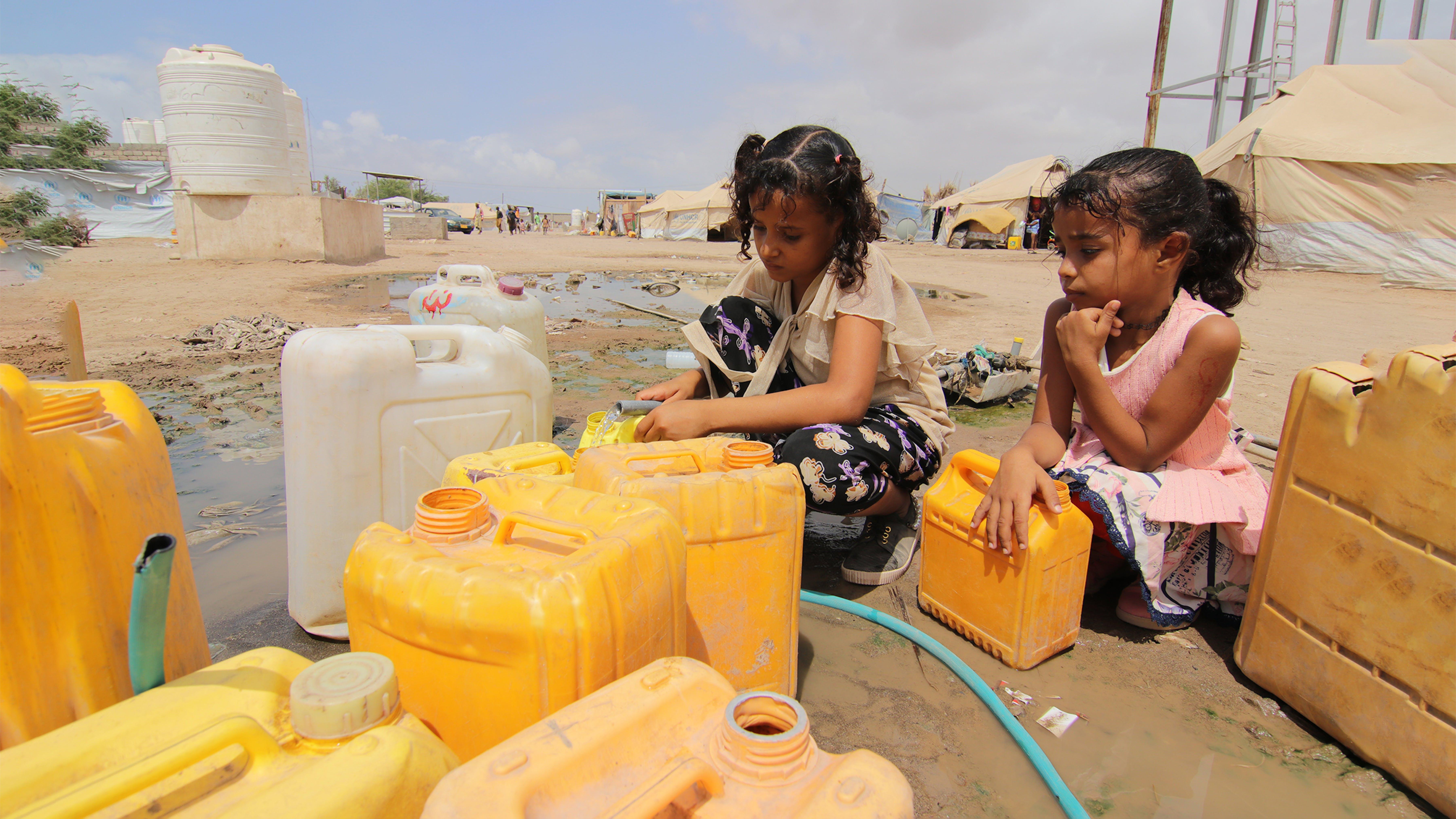 Yemen, due bambine riempiono le taniche di acqua pulita