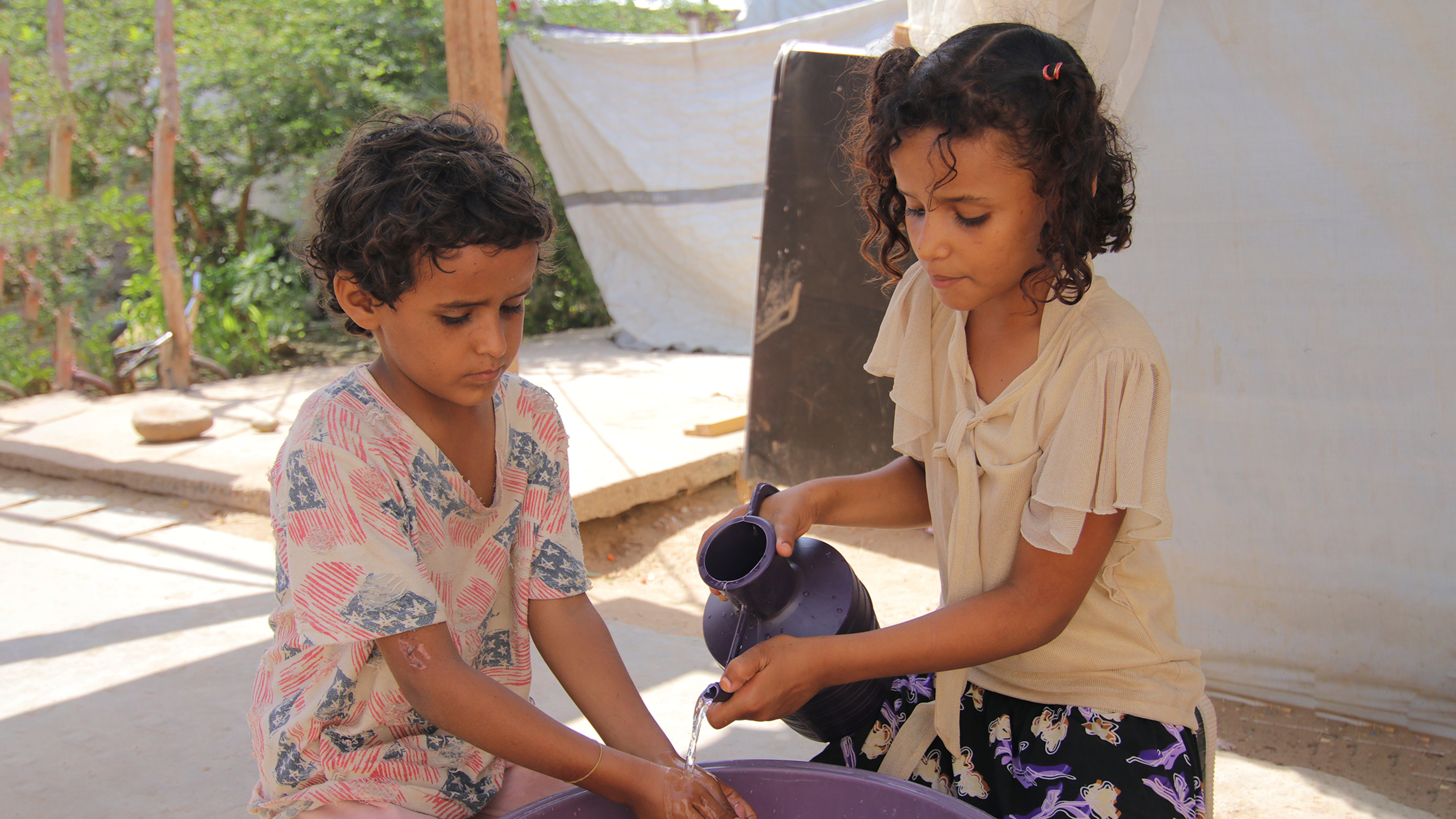 Yemen, bambini lavano le verdure prima di cucinarle