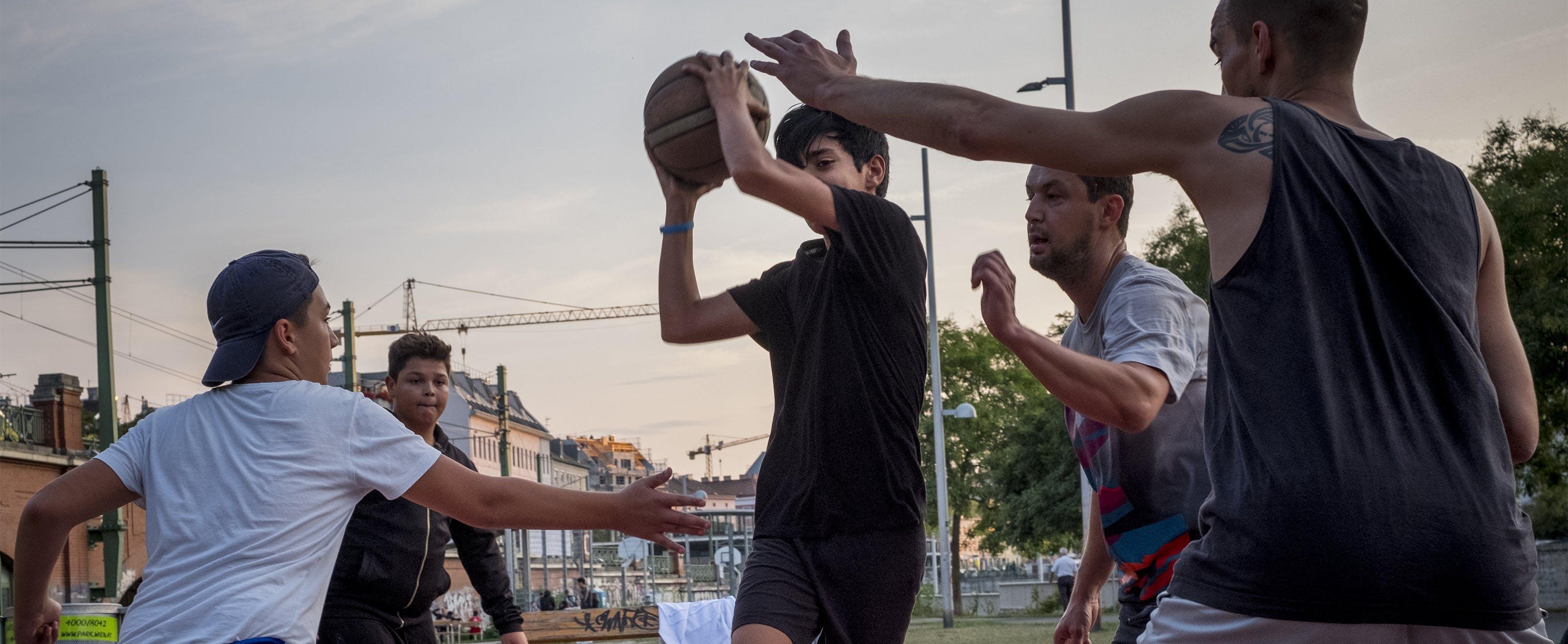Un adolescente rifugiato gioca a basket con alcuni coetanei, in Austria