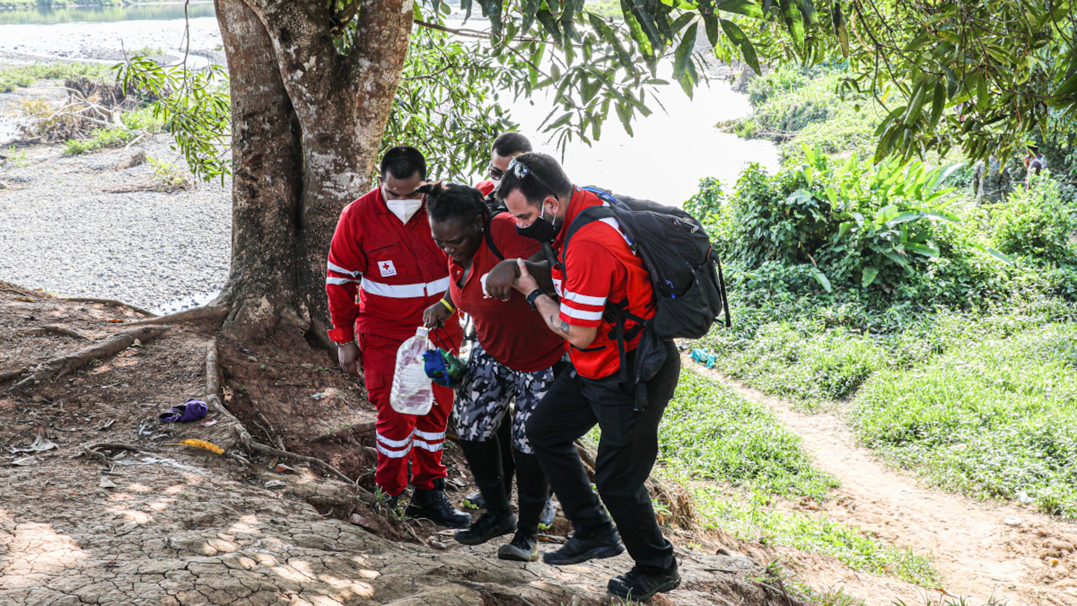 Panama, operatori della croce rossa panamense aiutano una migrante esausta al termine del lungo viaggio