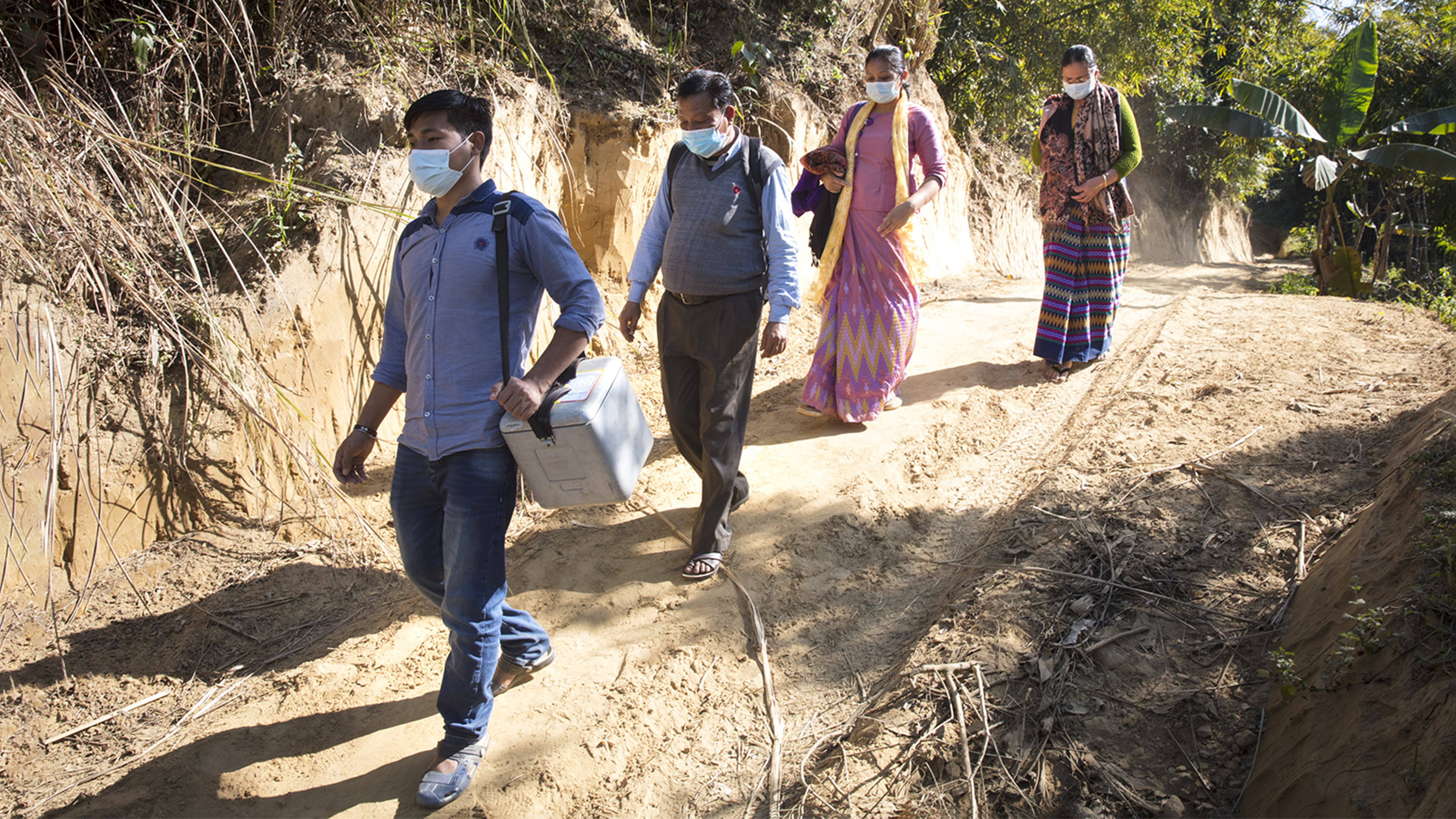 Yochingnu e il resto dello staff trasportano a piedi i vaccini nella zona di Rangamati, in Bangladesh.