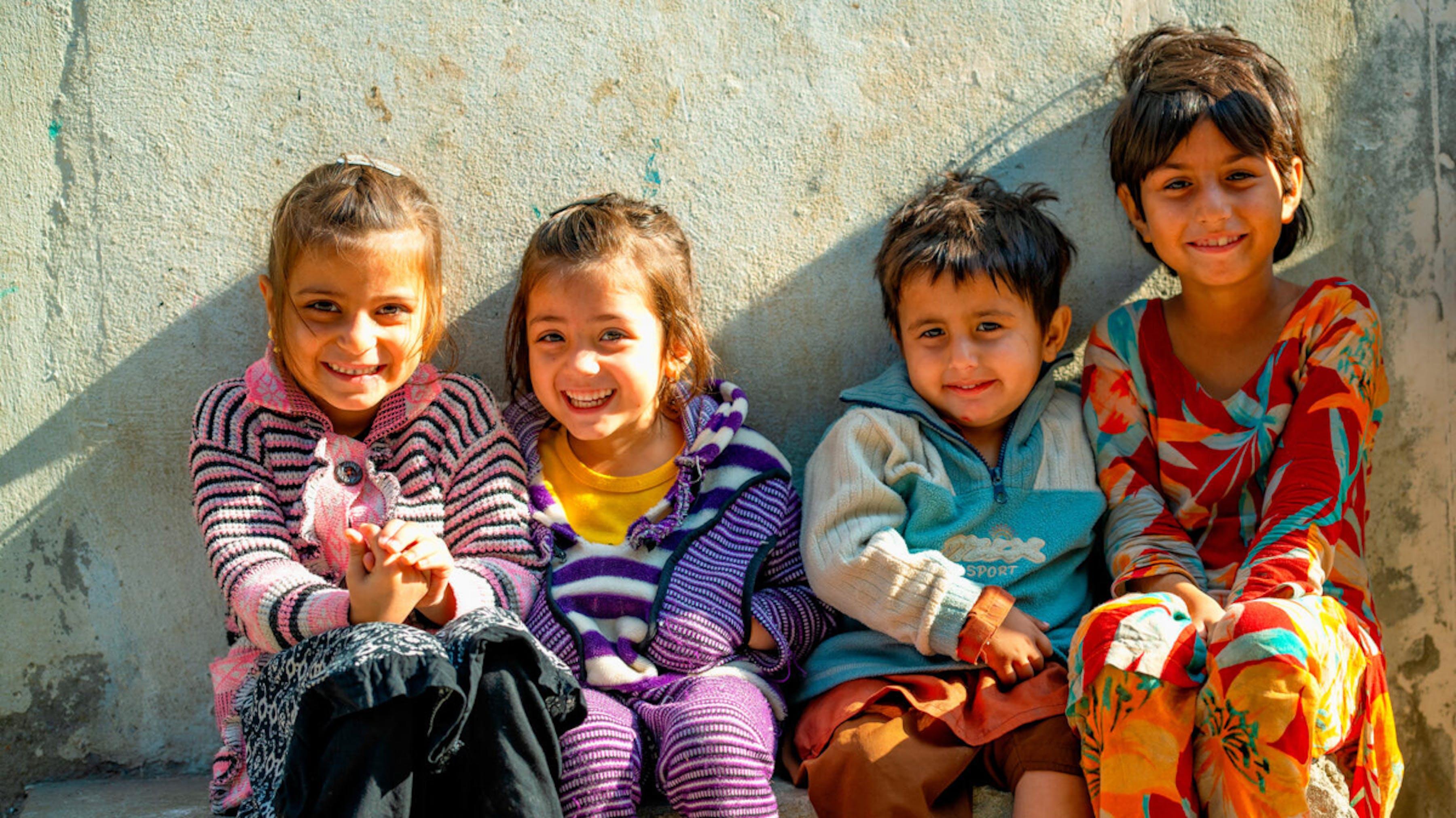 I bambini di Lahore, in Pakistan, accolgono con grandi sorrisi il team di vaccinazione antipolio.