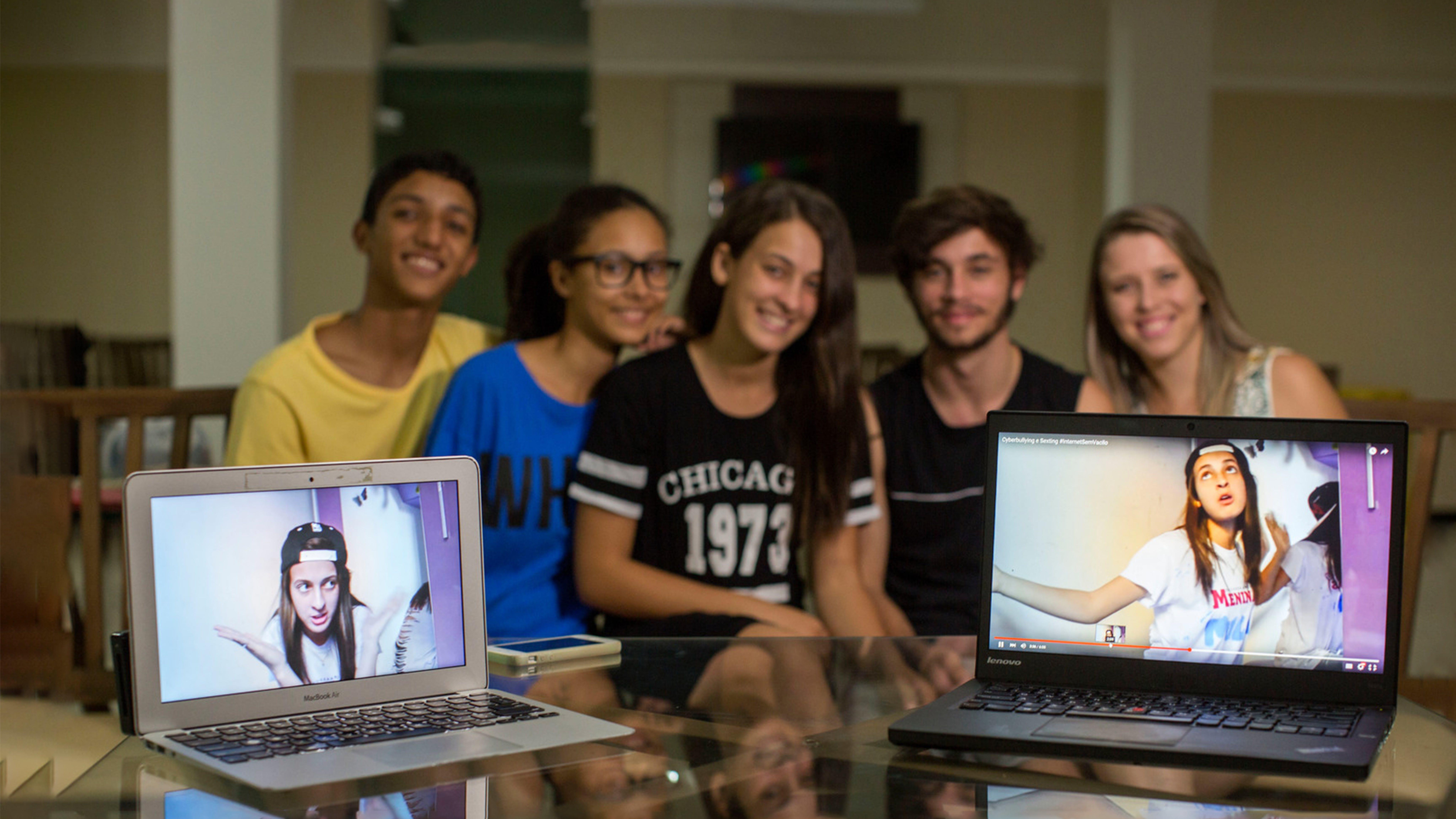Brasile, un gruppo di adolescenti con due pc che mostrano il video su come difendersi dal cyberbullismo