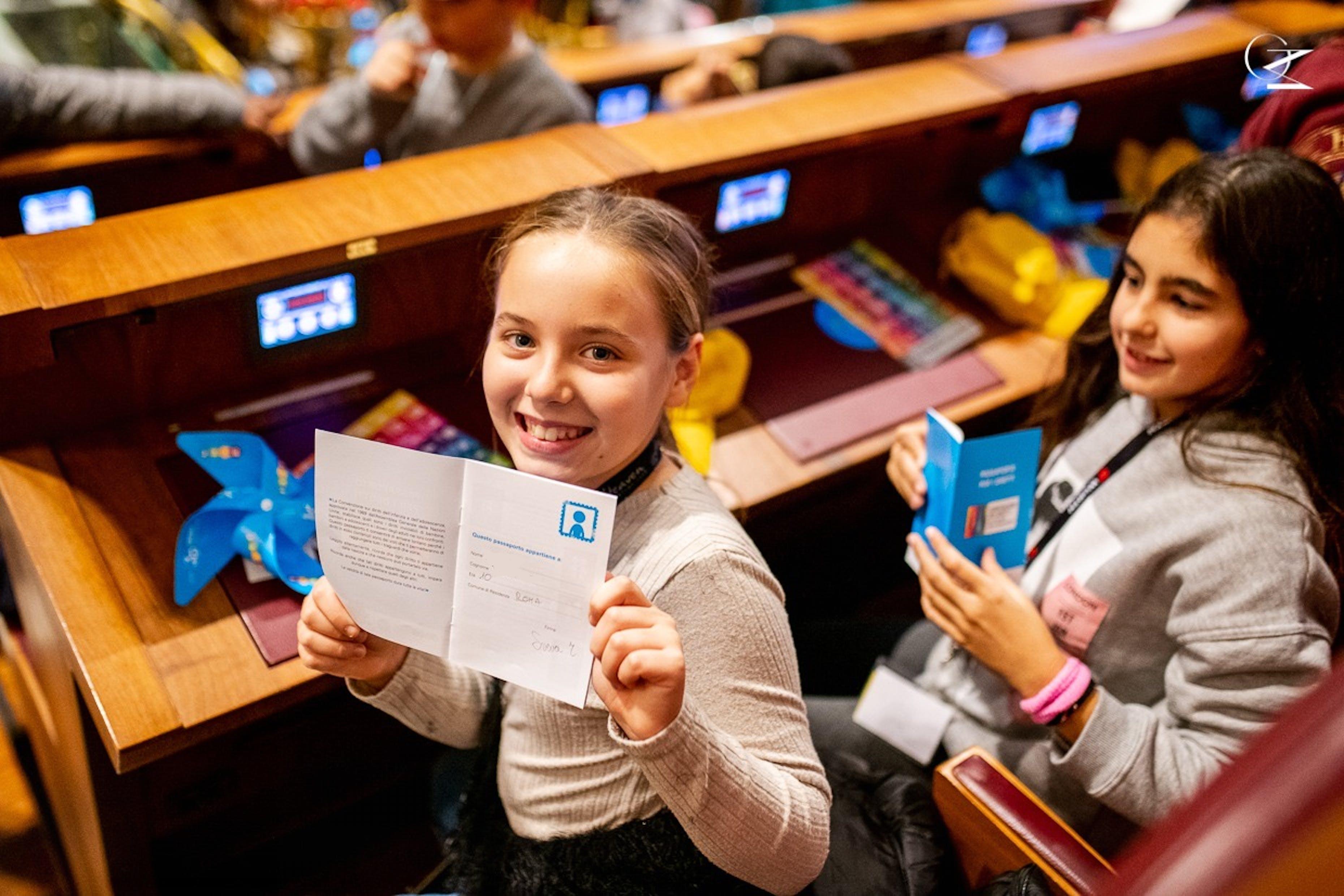 Una bambina mostra il Passaporto dei Diritti, pubblicato in occasione del 20 novembre 2019