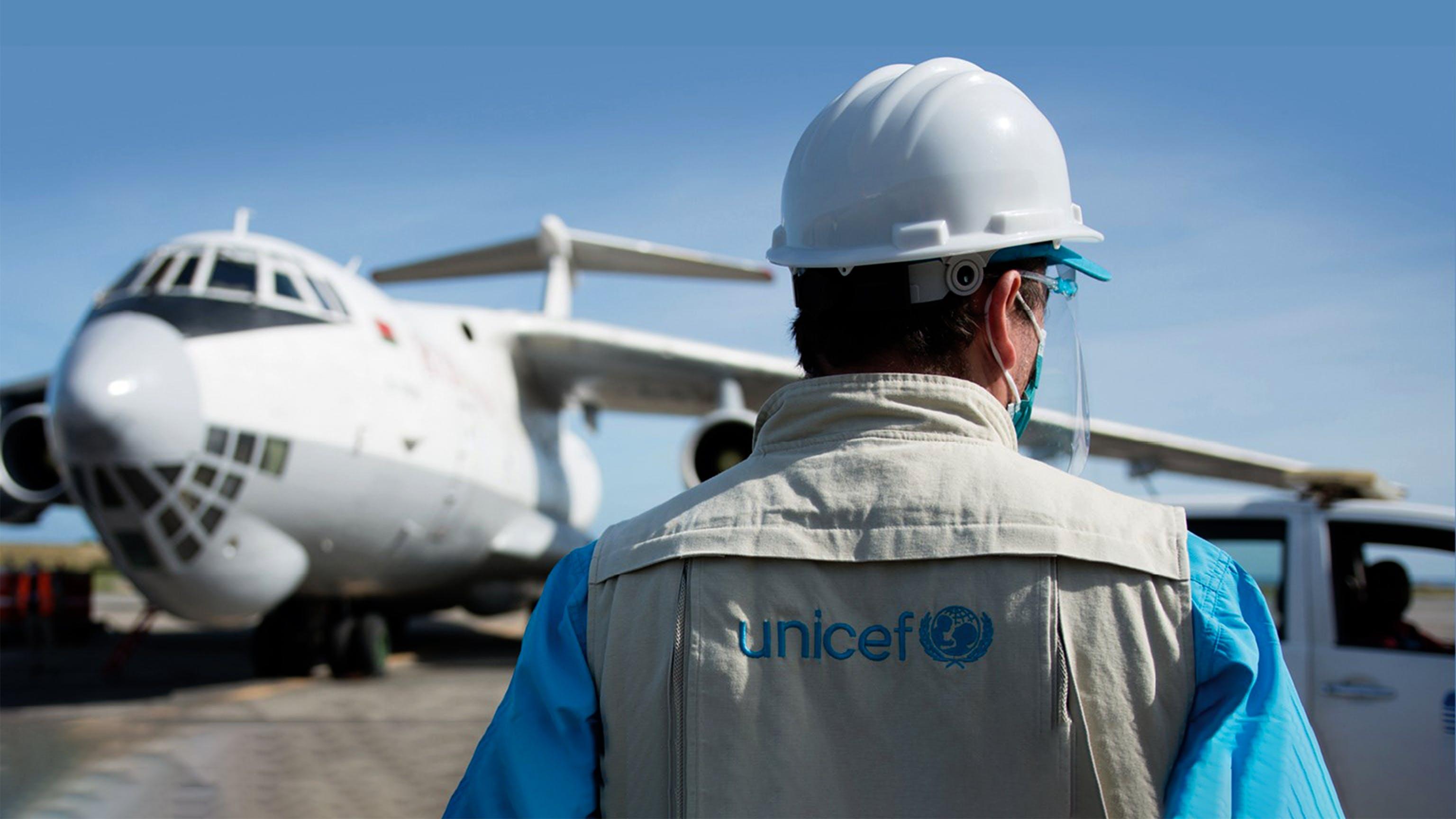 Un operatore UNICEF aspetta che venga scaricato l'aereo con le forniture COVAX