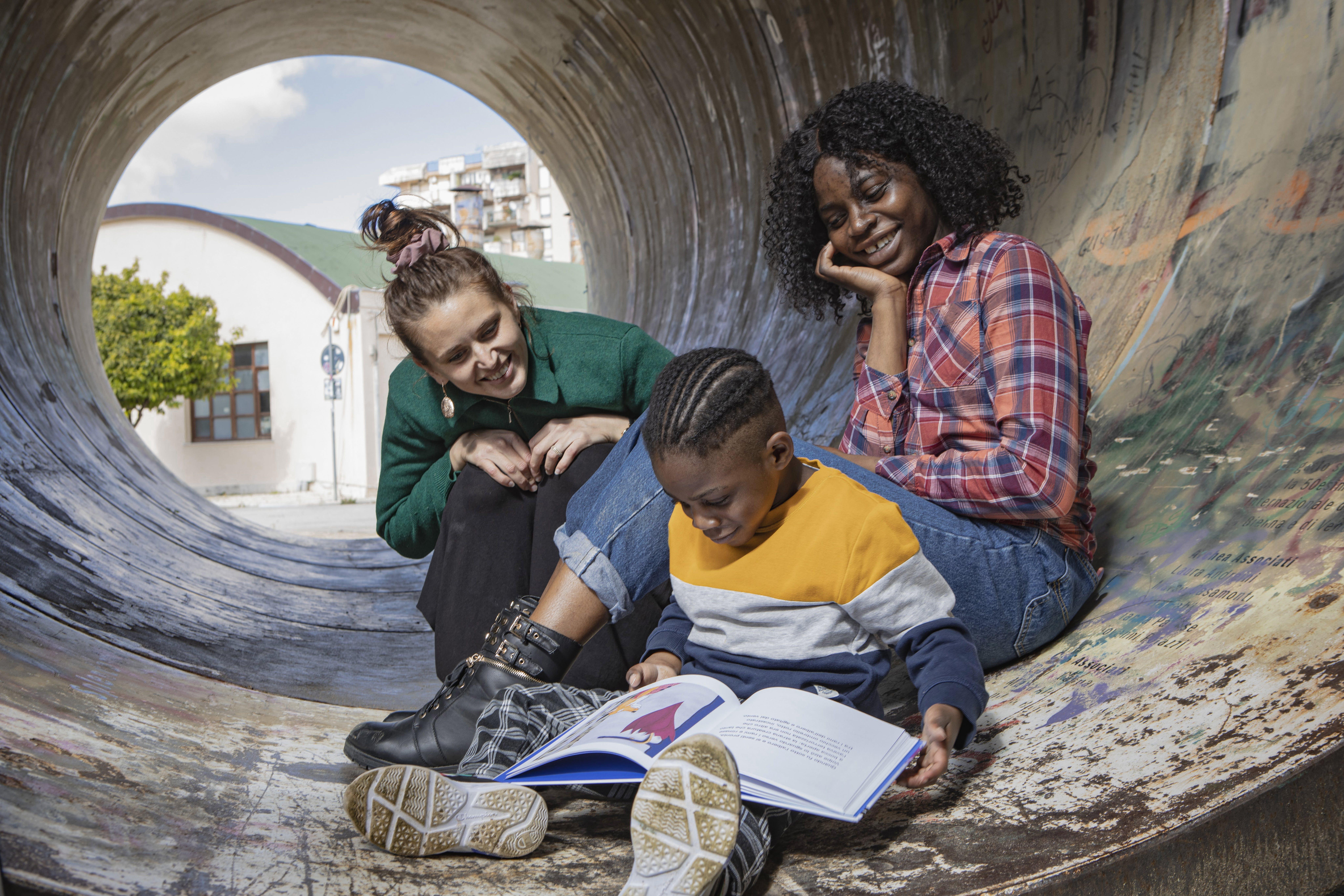 Vittoria e Valentina guardano il piccolo Christian mentre legge un libro