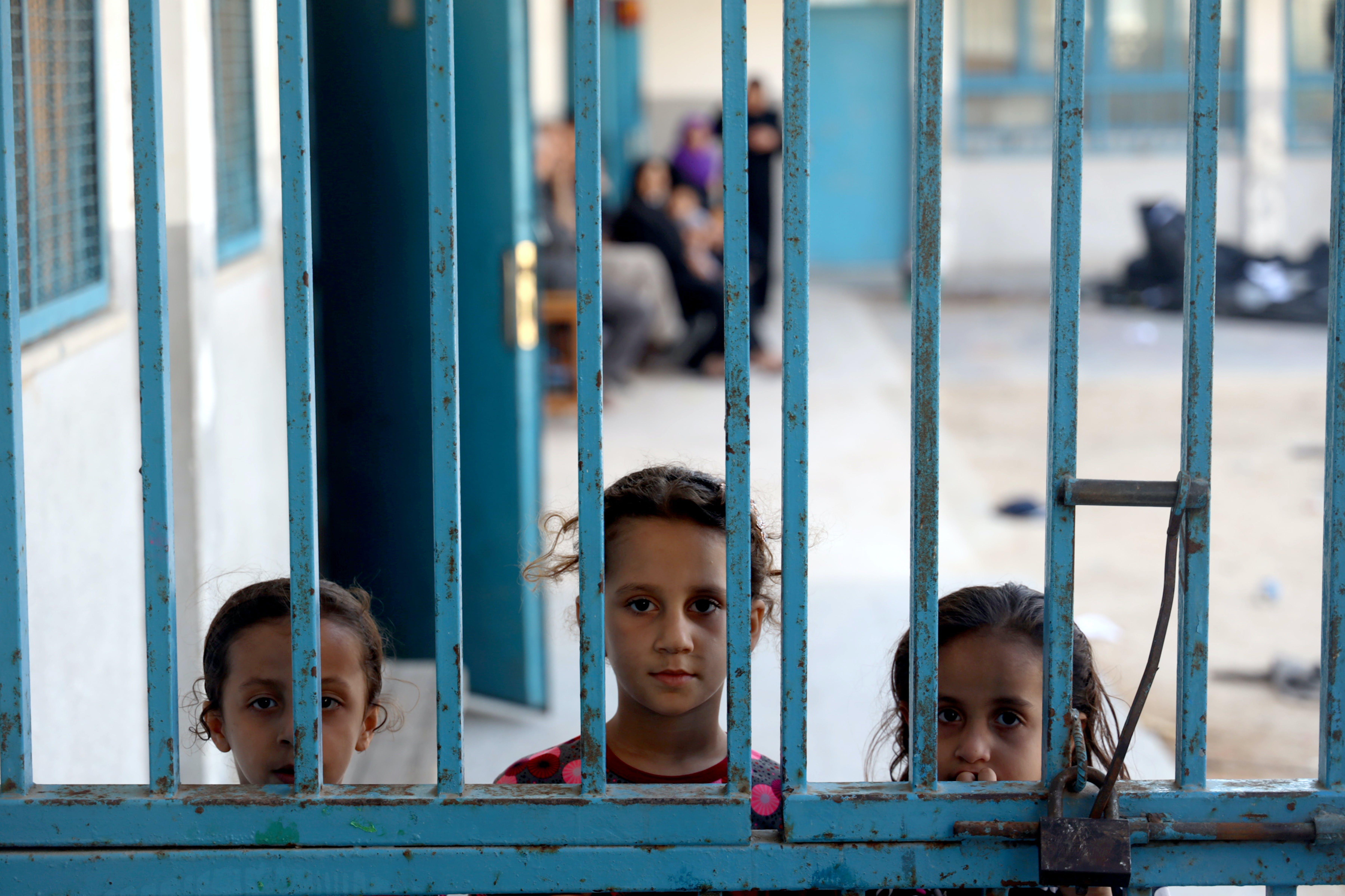 Tre bambine a Gaza guardano da un cancello di una delle 29 scuole dell'UNRWA usate come rifugio a causa dei pesanti bombardamenti.