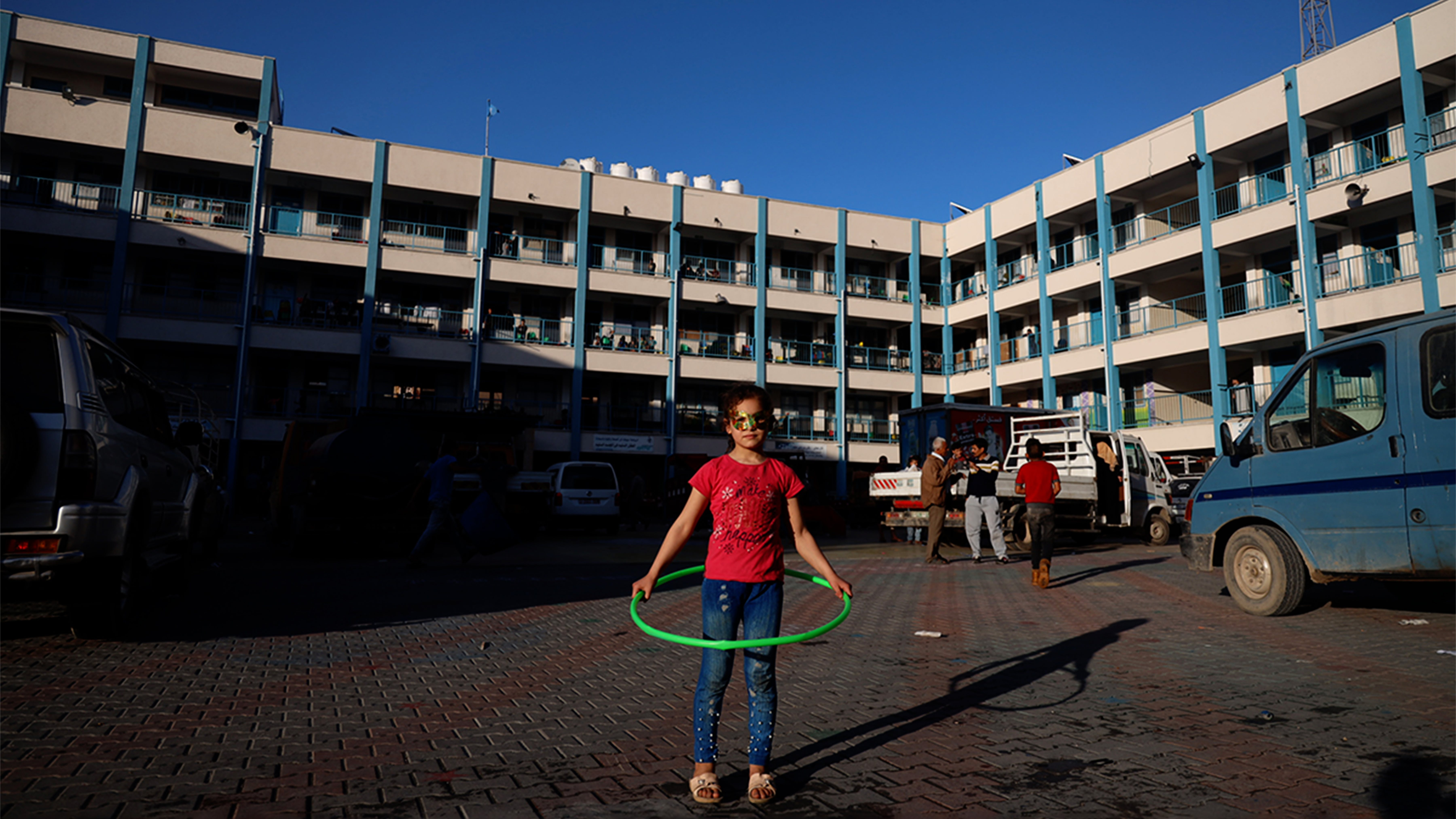 Una ragazza palestinese gioca nel cortile di una scuola dell'UNRWA nella Striscia di Gaza, attualmente utilizzate come rifugio temporaneo