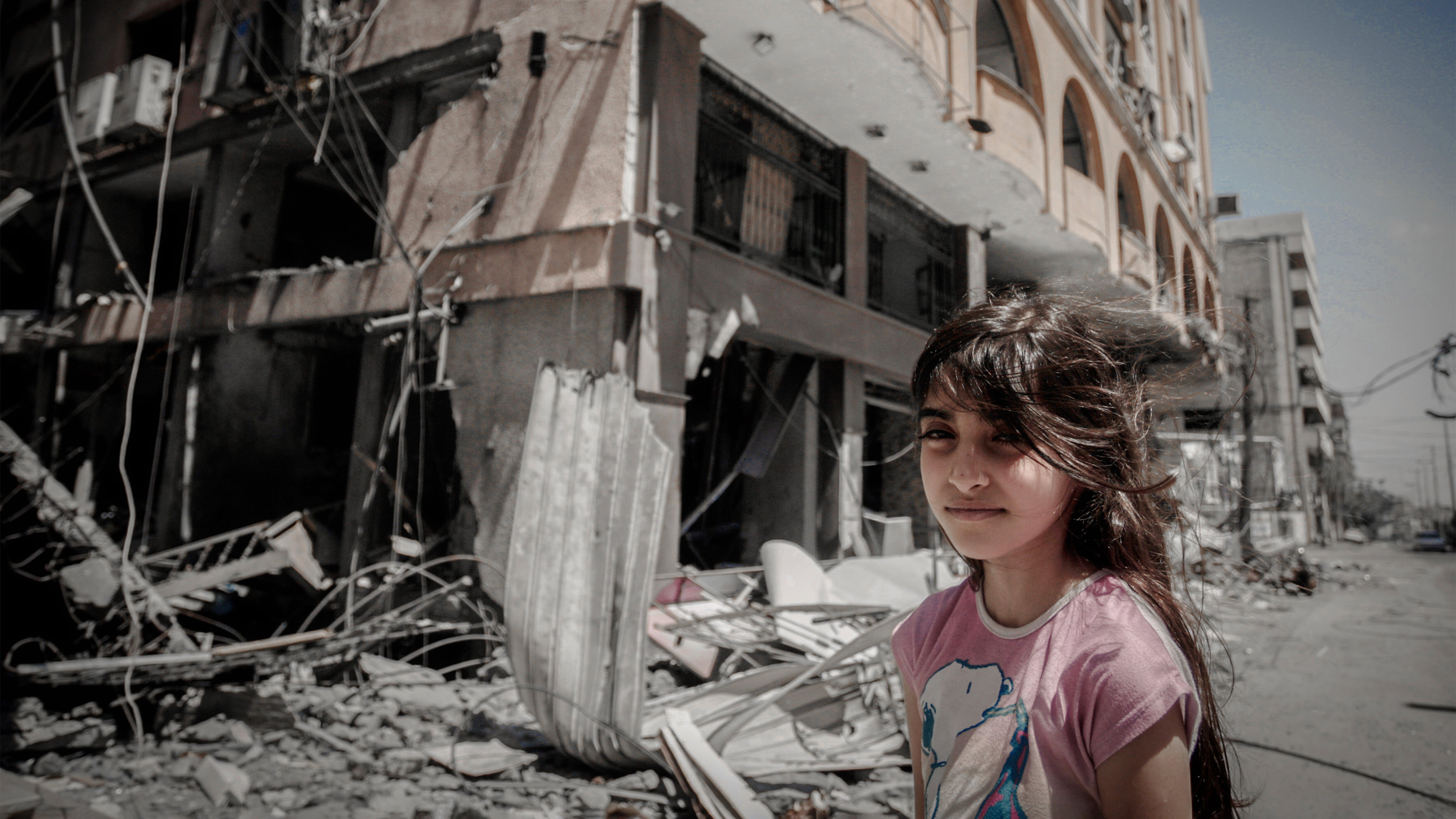 una ragazza palestinese è in piedi davanti alla loro casa mentre la sua famiglia estrae i suoi beni dall'interno della loro casa danneggiata dopo essere stata presa di mira a Gaza City.