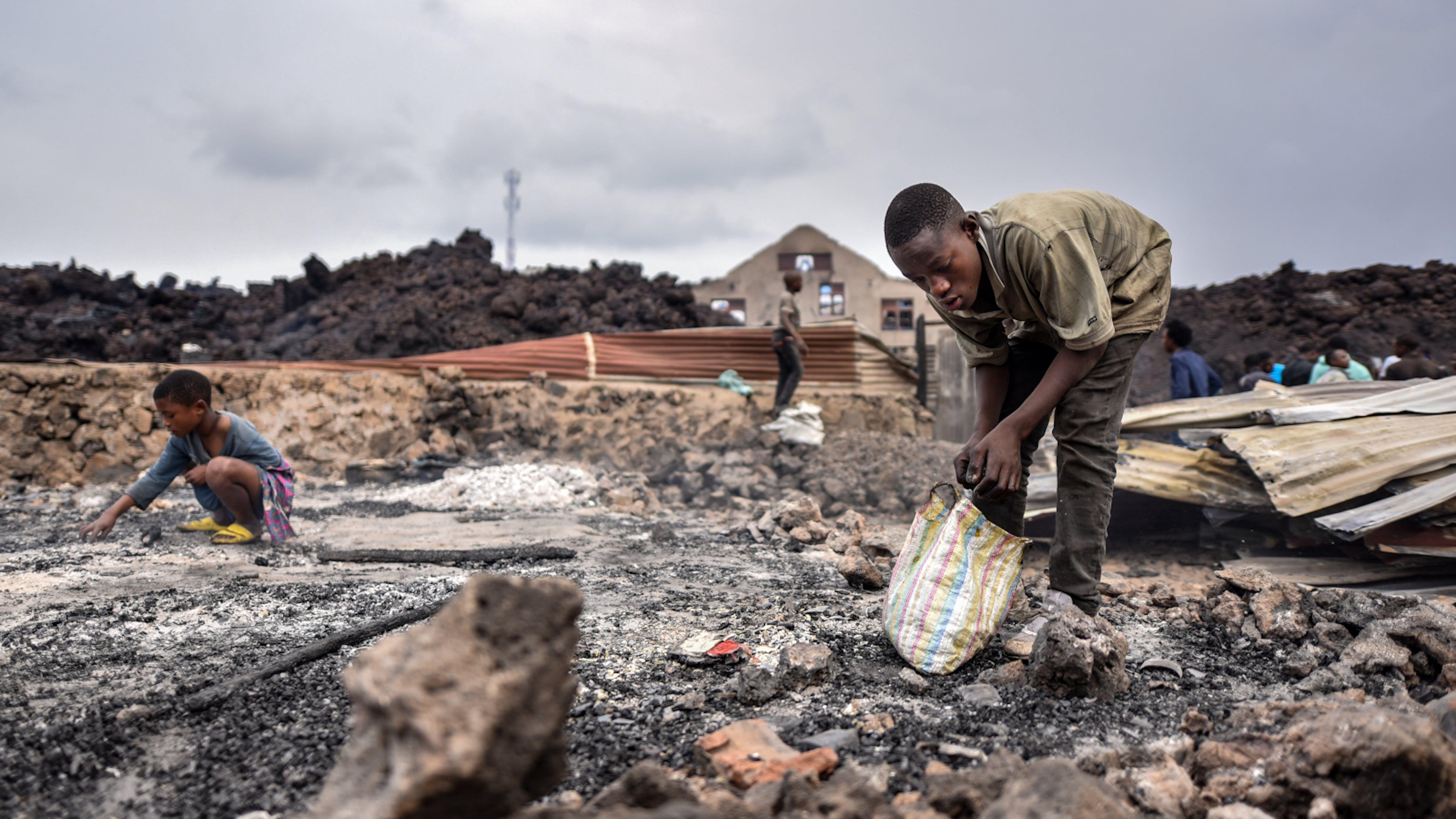 Alcuni bambini raccolgono ciò che resta delle loro cose dopo l'eruzione del vulcano Nyiragongo a Goma