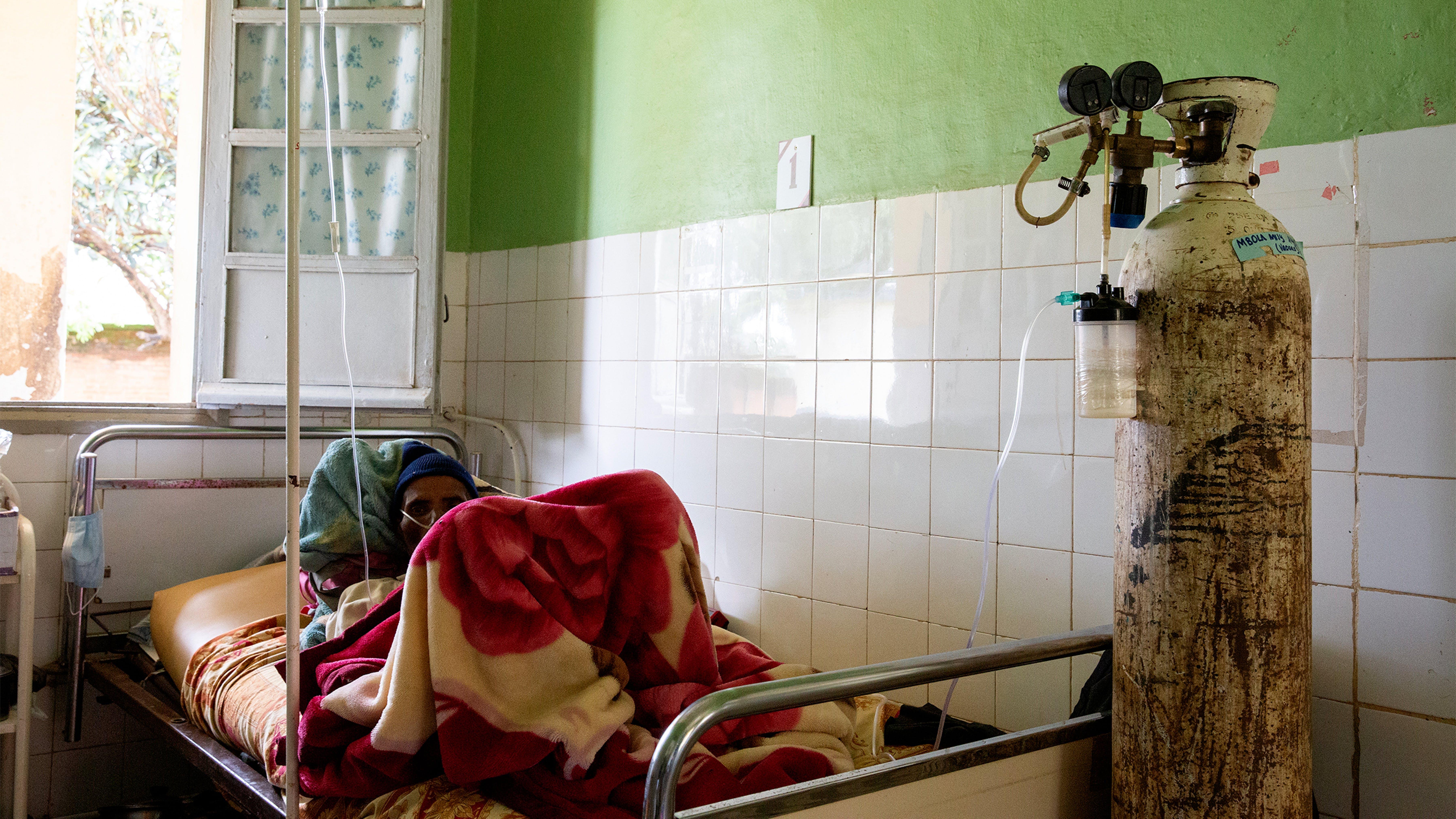 Madagascar, una paziente sdraiata ha ai piedi una bombola di ossigeno