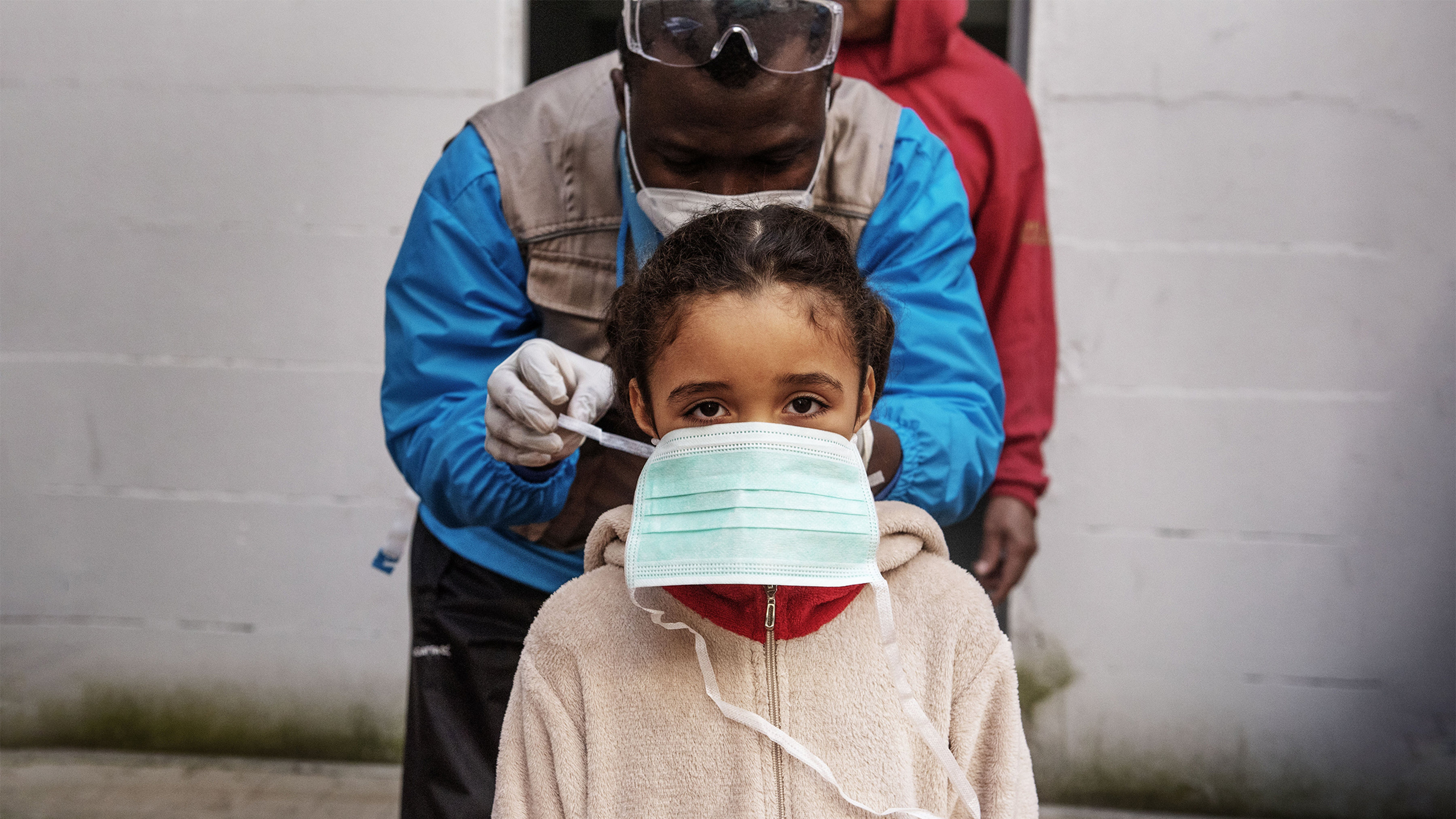 na bambina aiutata con una mascherina protettiva