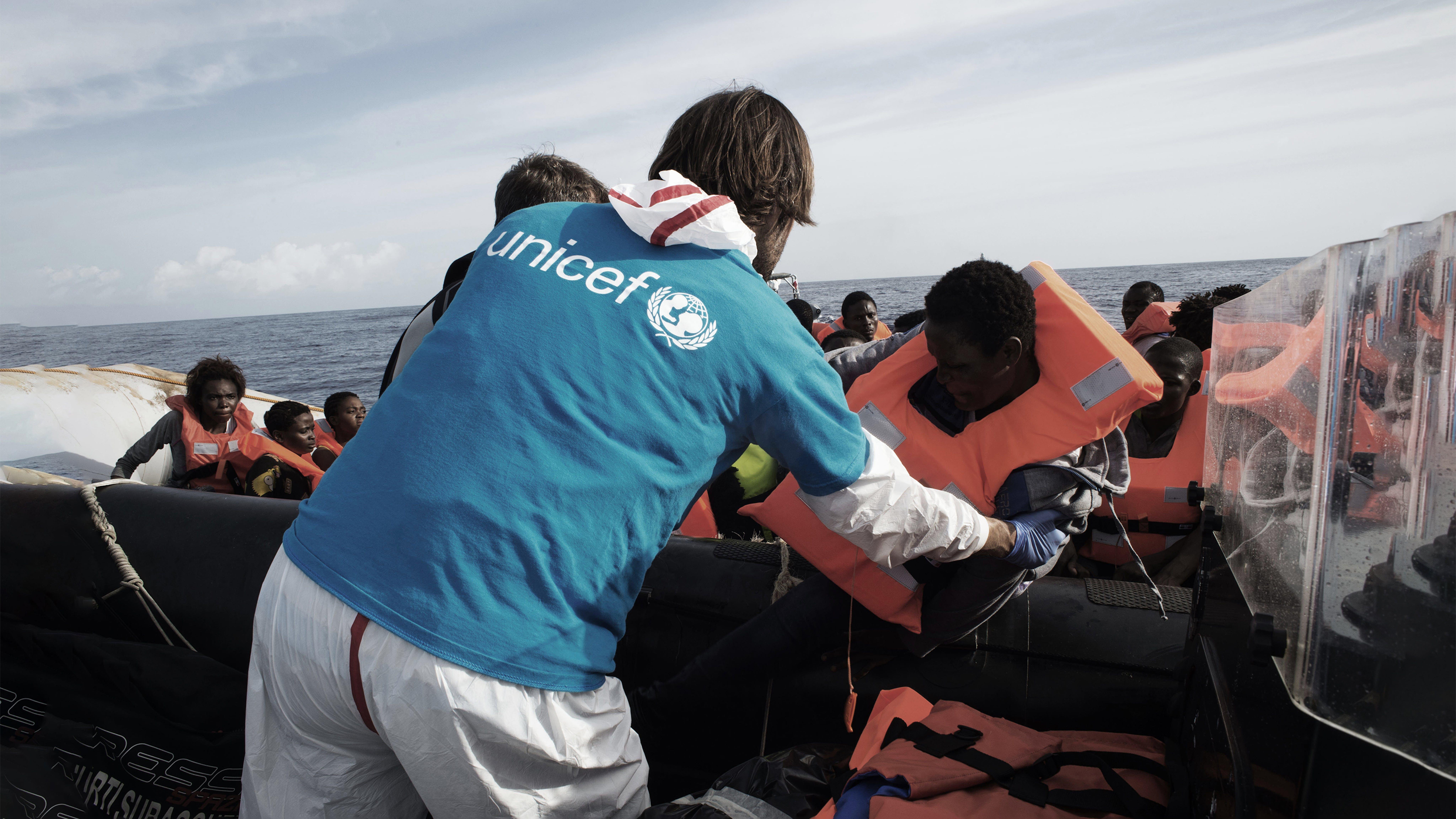 Un volontario italiano aiutare i migranti a trasferirsi dal gommone alla nave Fasan della Marina Militare