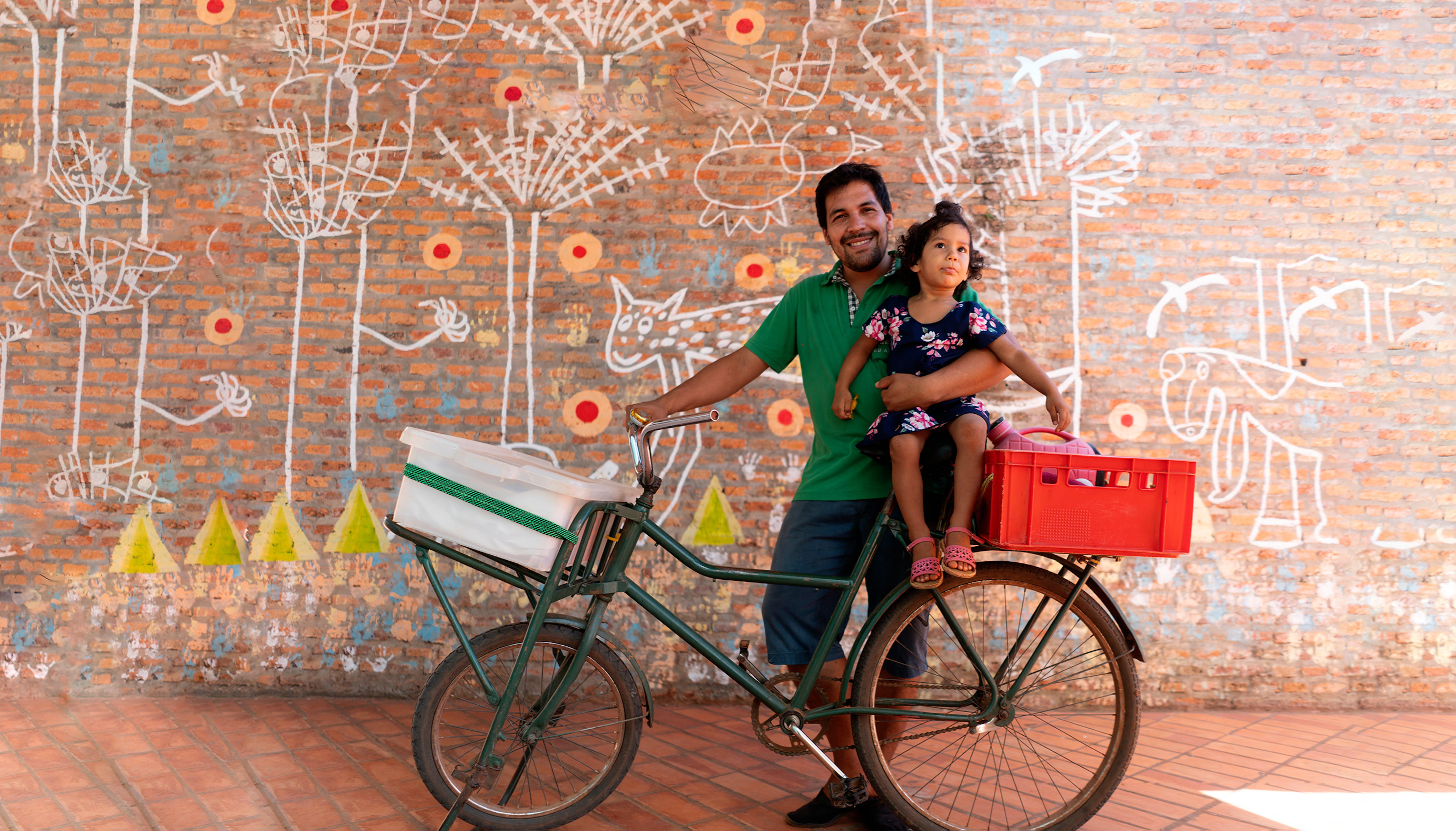 Paraguay. Rafael tiene in braccio sua figlia , 2 anni, seduta sulla bici che lui e sua moglie utilizzano per spostarsi e per consegnare il pane a lavoro