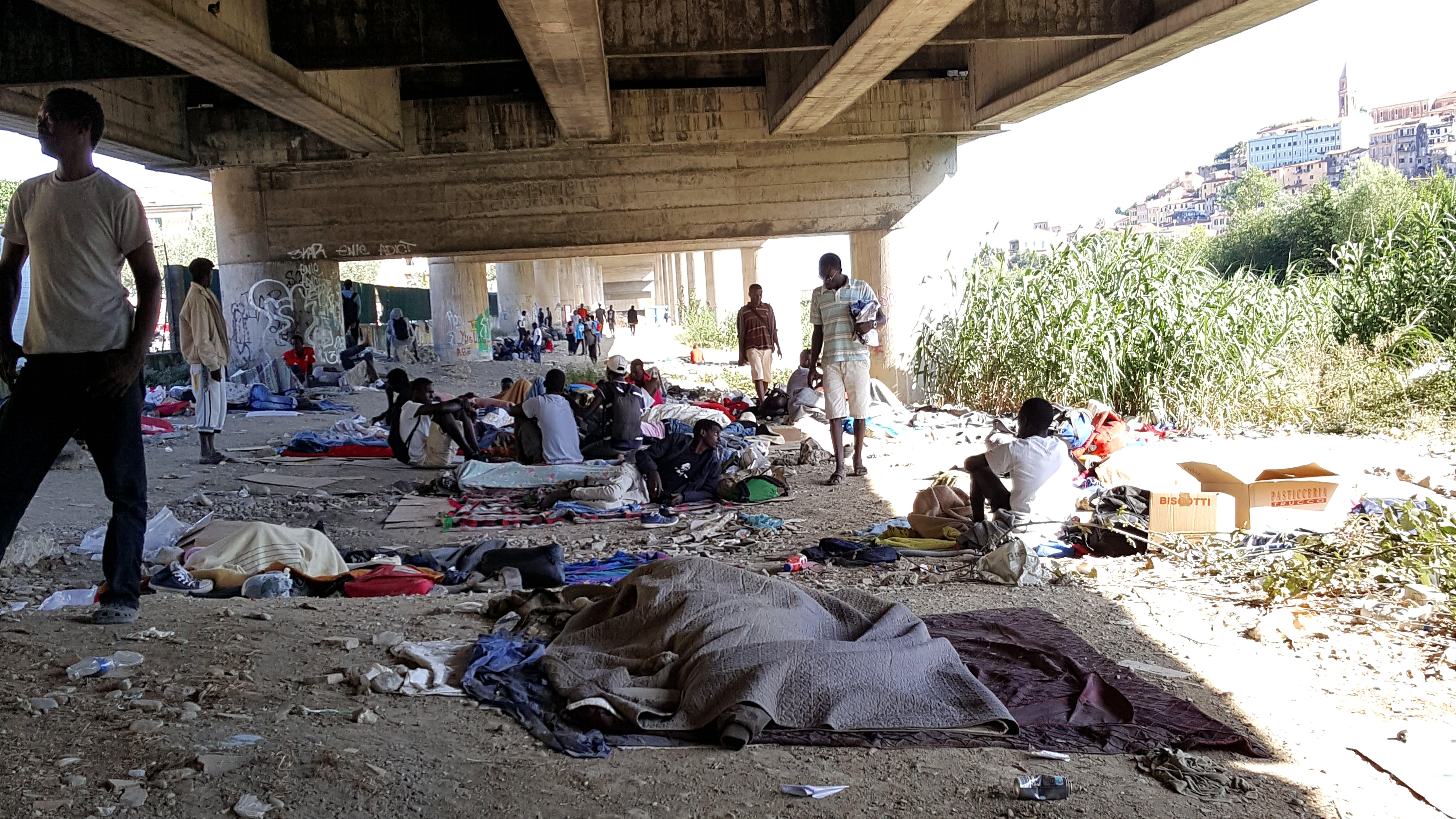 Foto d'archivio, migranti sulle sponde del fiume Roja in attesa di attraversare il confine con la Francia