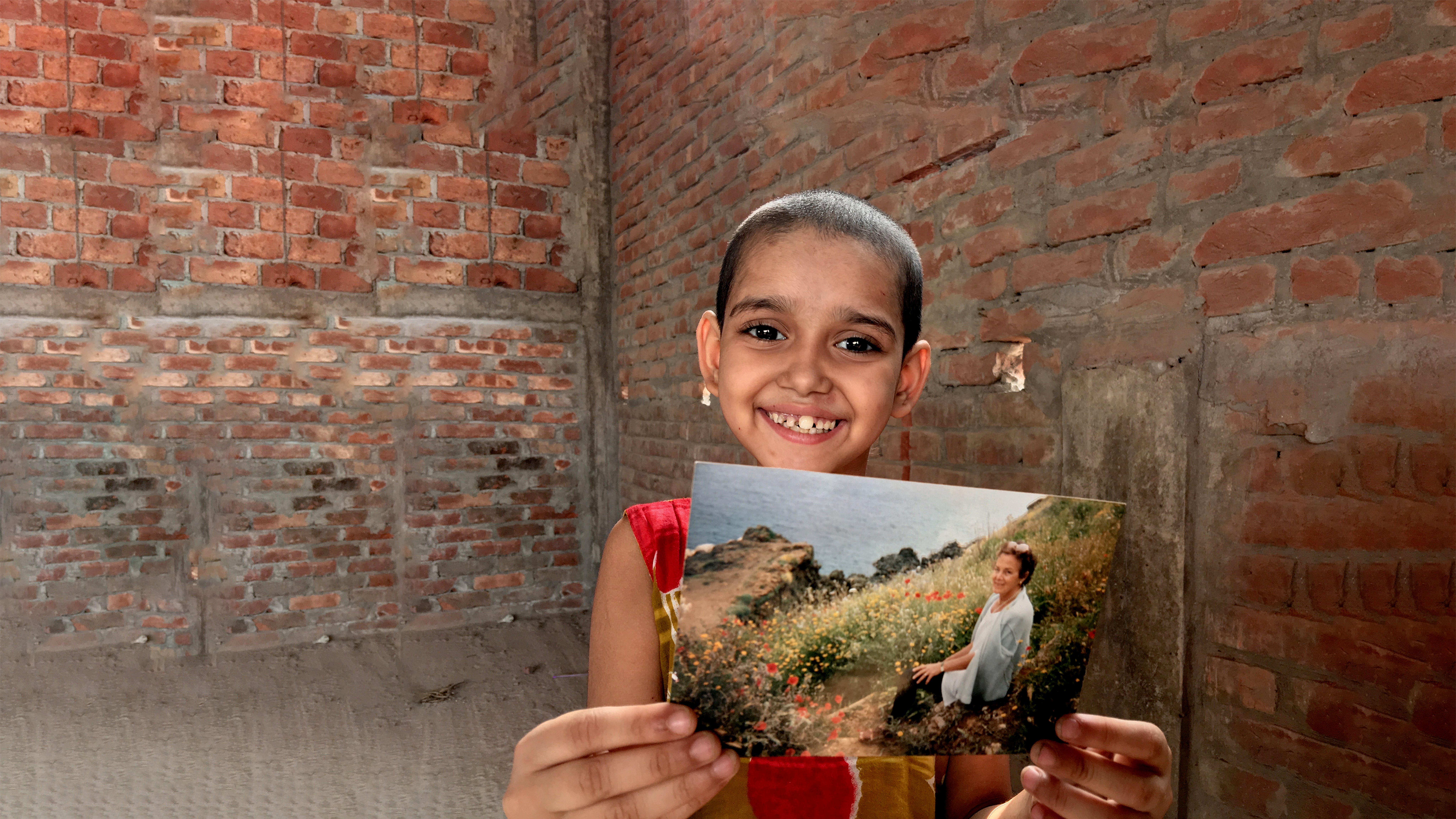 Bambina tiene in mano la foto di una donna - donazioni in memoria