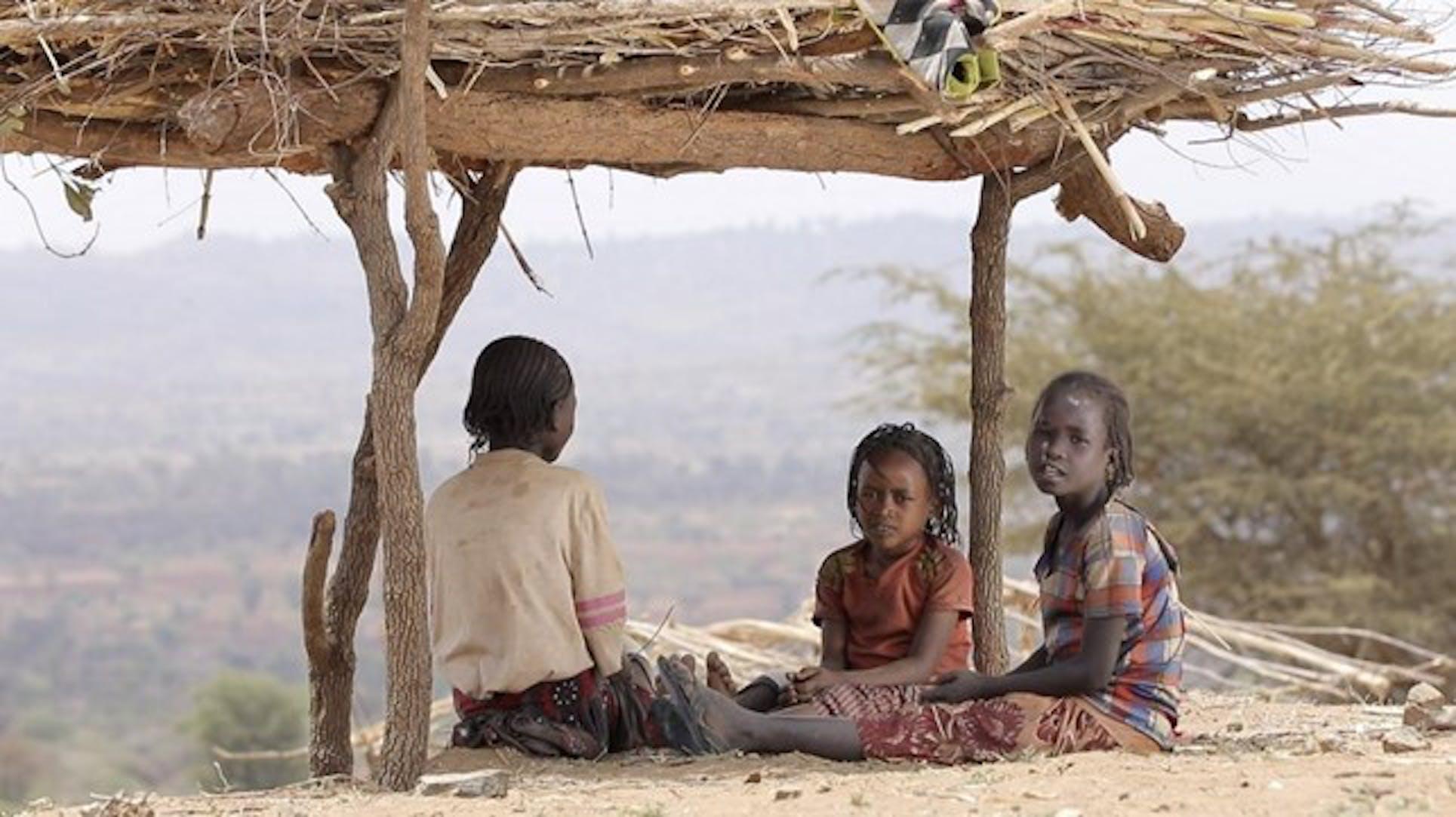 Bambini sfollati si riparano sotto una capanna di legno e paglia, in Etiopia