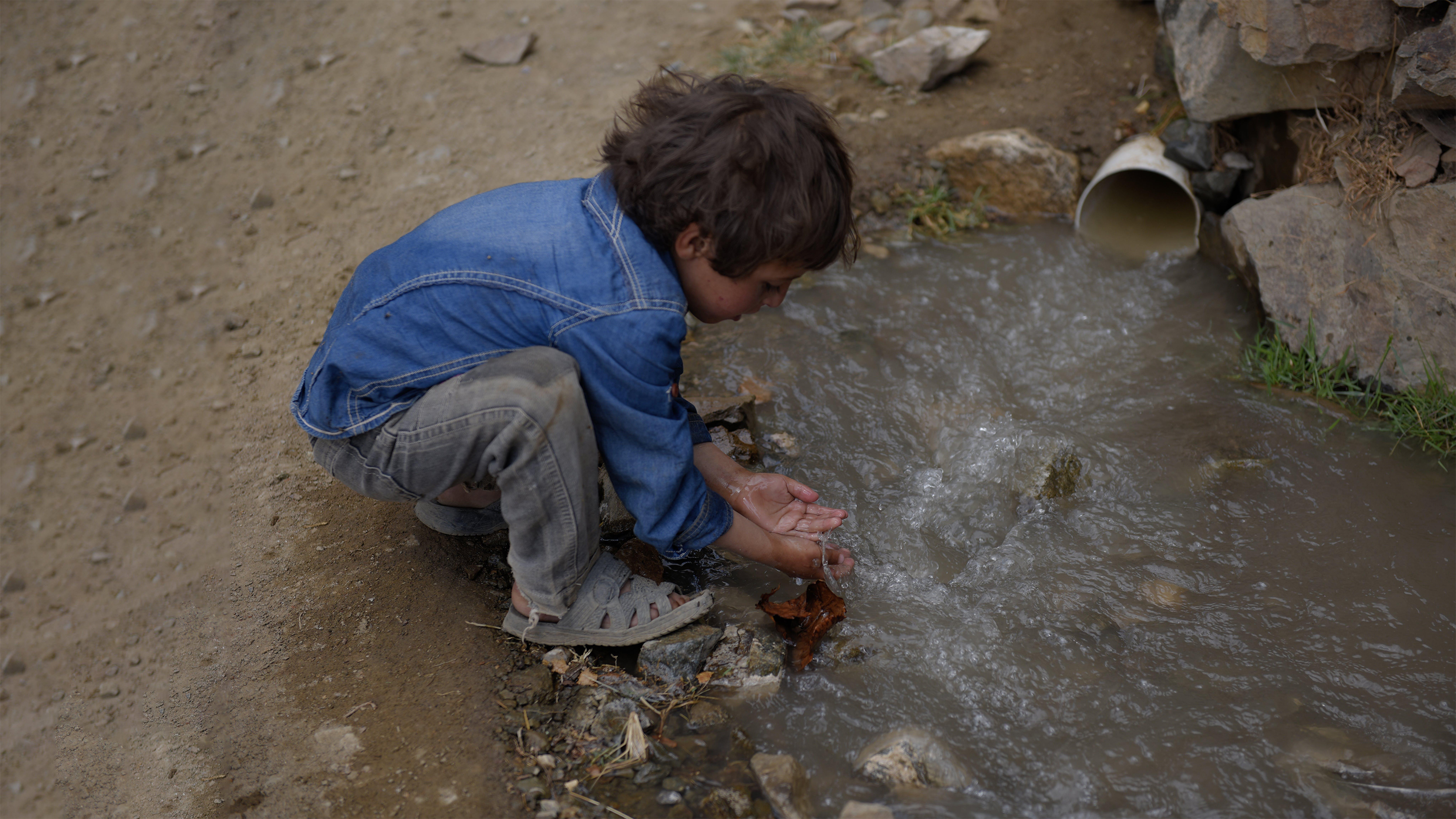Un bambino si lava le mani con acqua non trattata proveniente da un tubo di fognatura nel governatorato di Amran, Yemen,